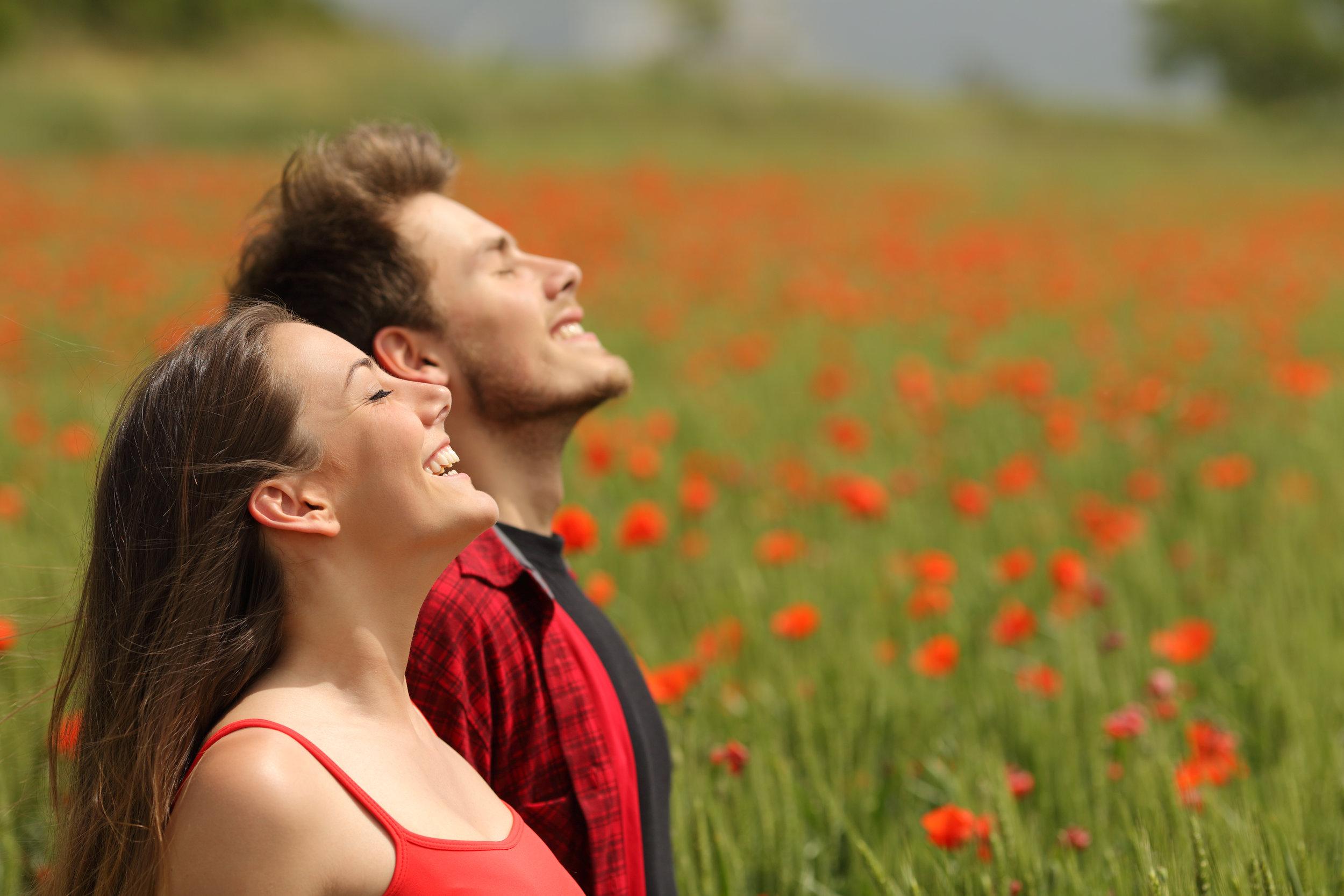 Happy couple breathing fresh air in a red field.jpg
