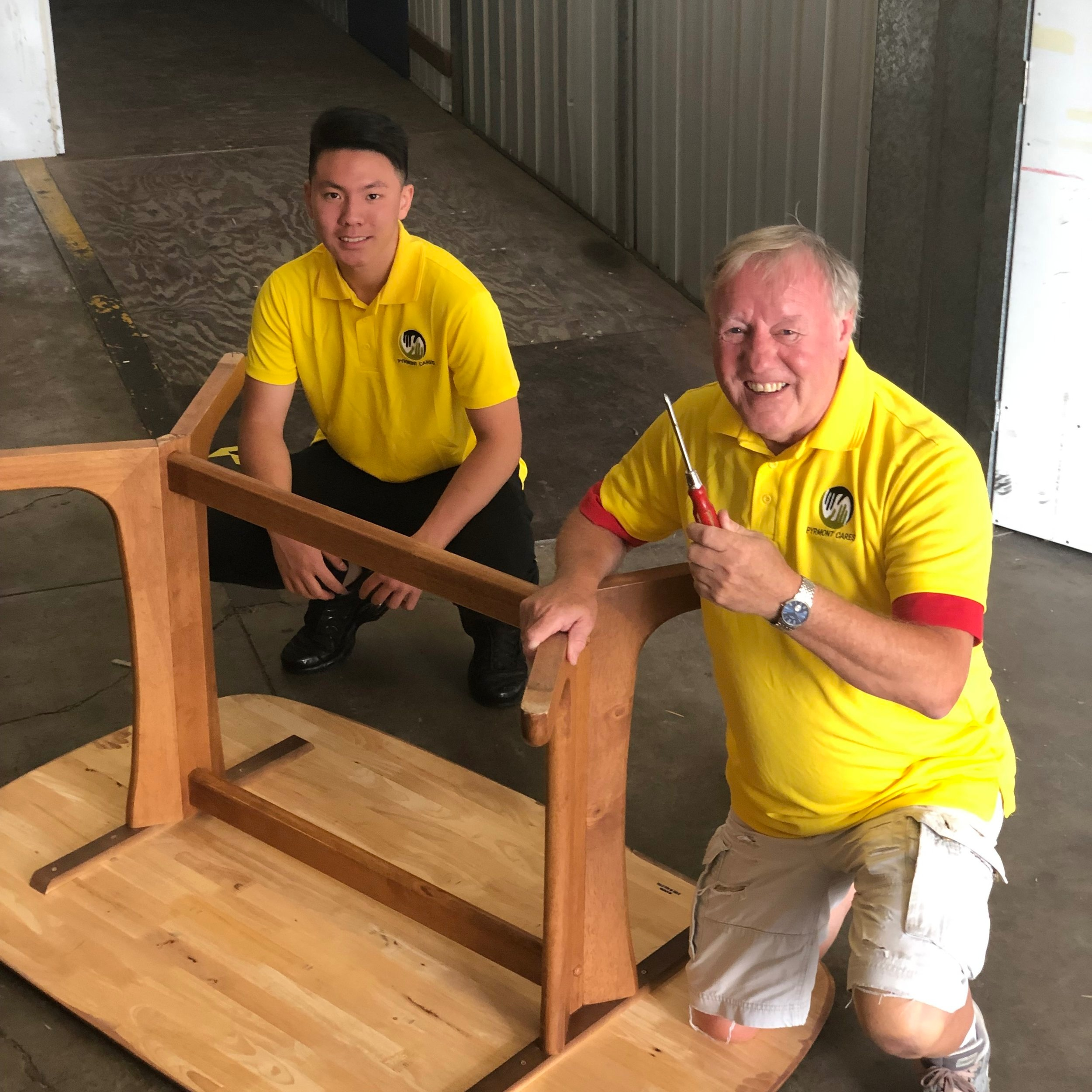 Volunteer Richard and Marcus assembling a table before dispatch.