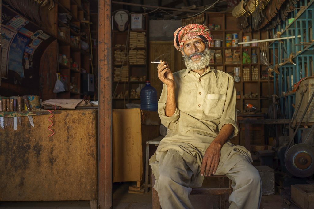 A man at a hardware store in Sahiwal, Pakistan takes a cigarette break (2015)