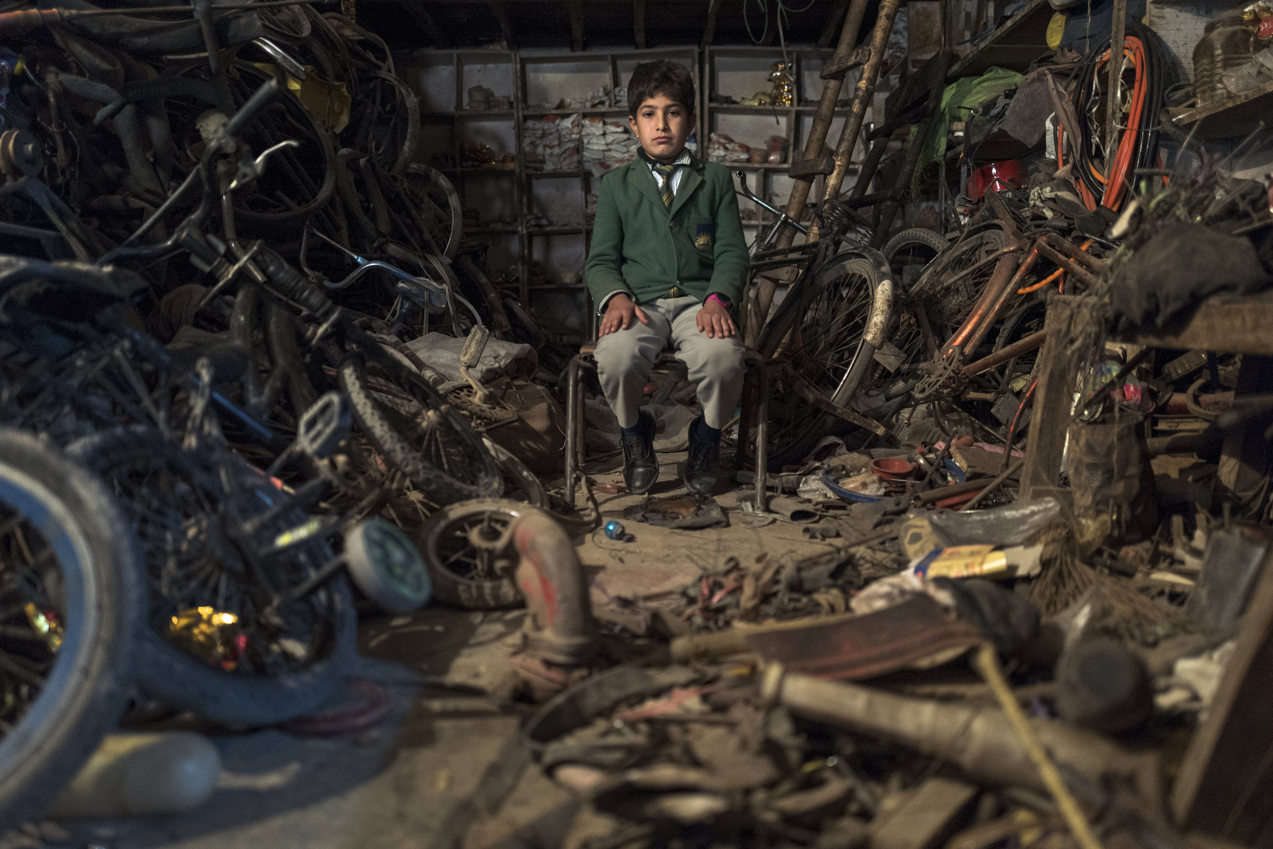 Schoolboy keeps watch at a bike repair shop