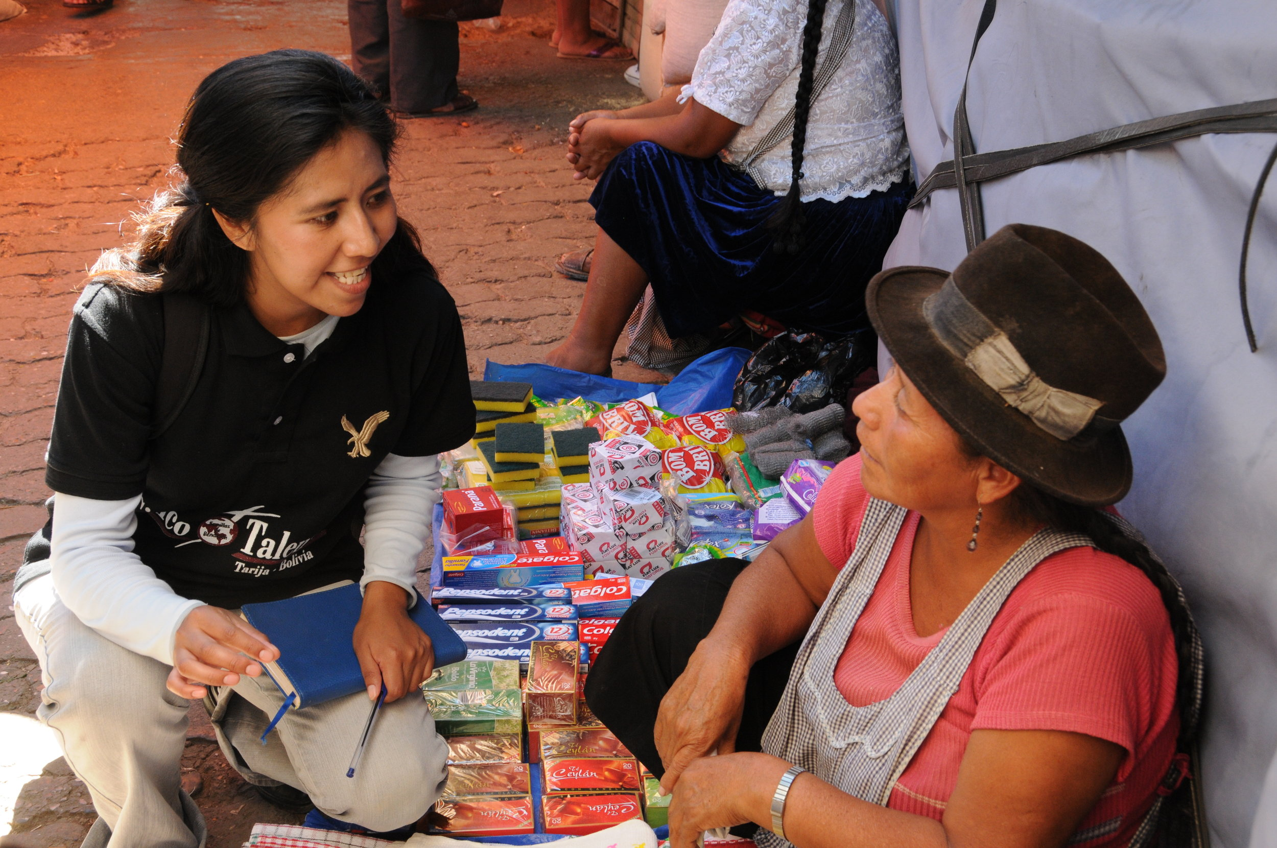 Bolivia's Training Coordinator, Eva (left), speaks to a member about her business.