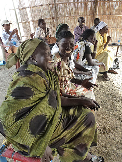 Women laugh at their group meeting in South Sudan.