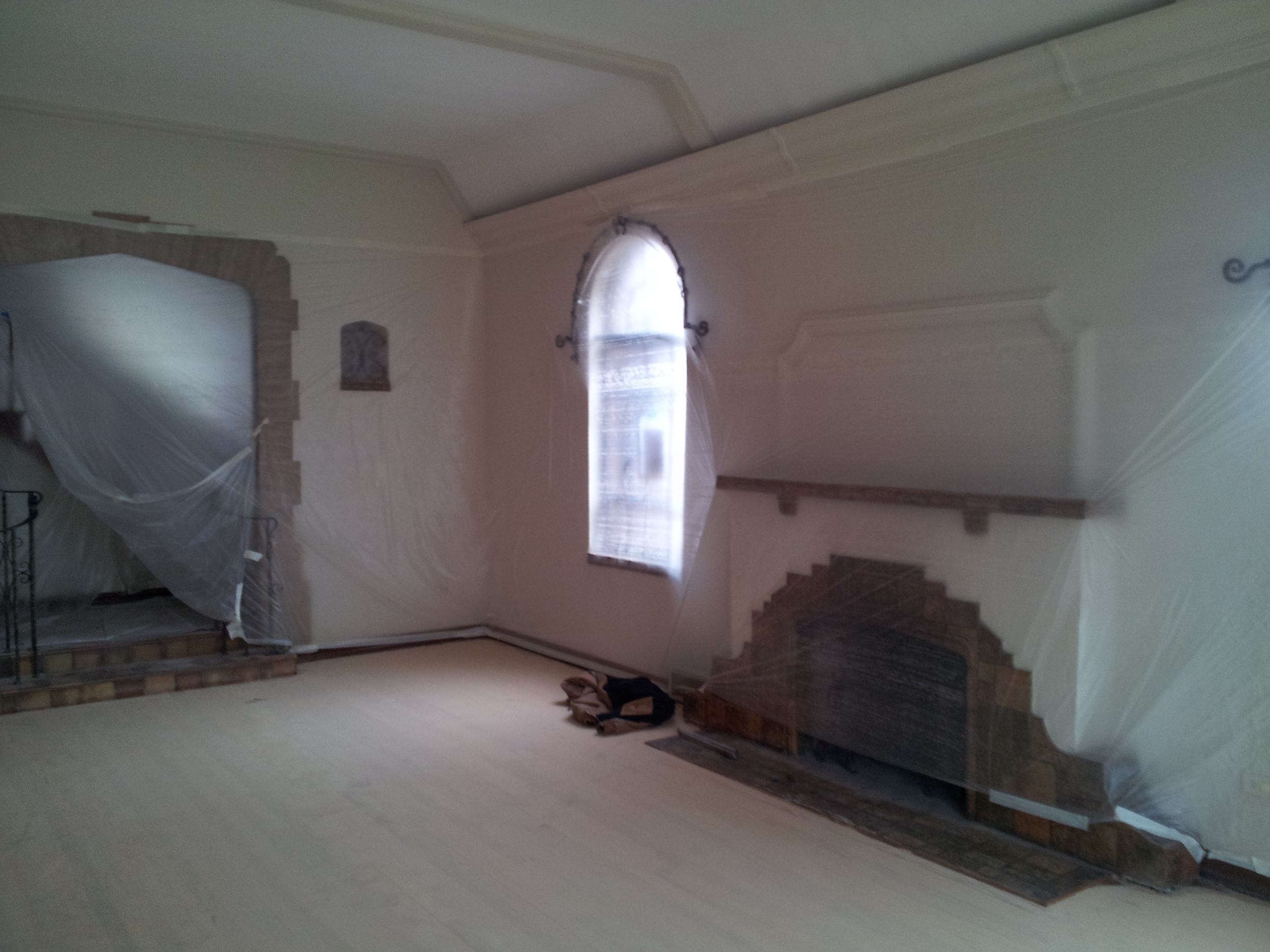 Architectural tudor archways. Refinishing hardwood floors, new plaster walls, new architectural archways, new tile, new ornamental guardrails, new crown molding.