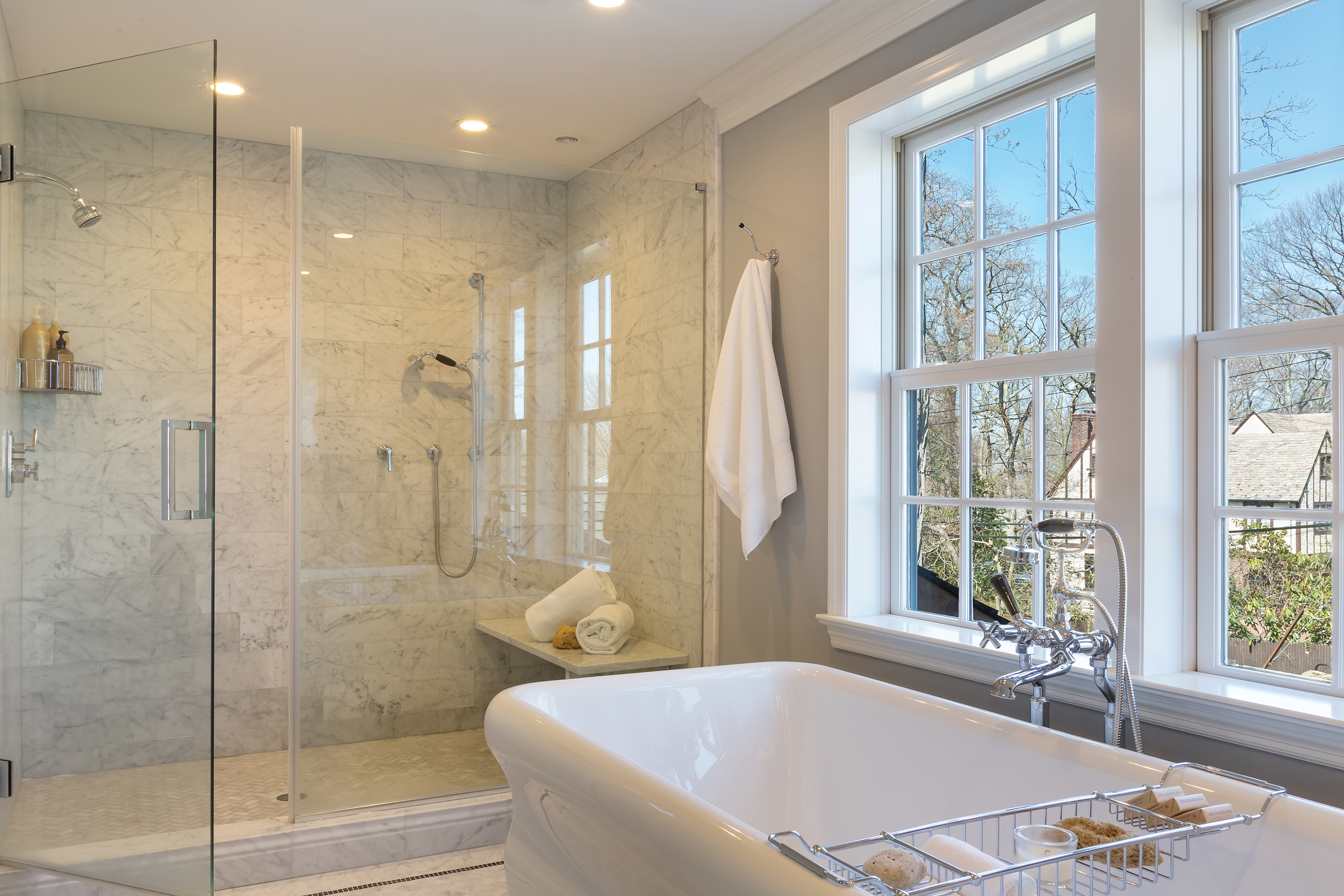 Tom Fox designed a spacious shower that runs the width of the room as he did with the vanity wall. Custom-designed Carrara marble throughout with a seamless glass enclosure creates optimal visual space. At one end is a showerhead; at the other, a hand-held shower is flexible whether standing or sitting.