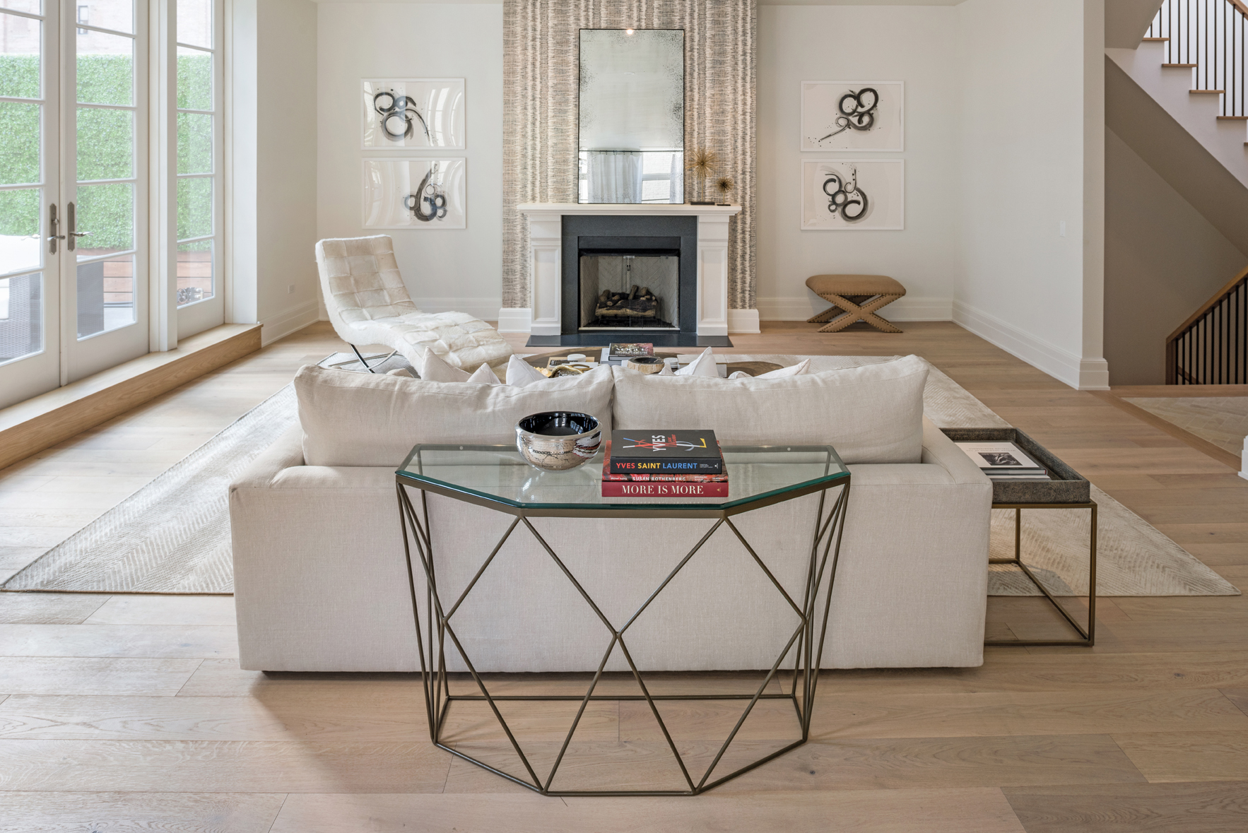 The custom artwork of this living space brings attention directly to the fireplace, which is extended in size and effect through the wallpaper detail and use of a mirror to extend the length of the room.