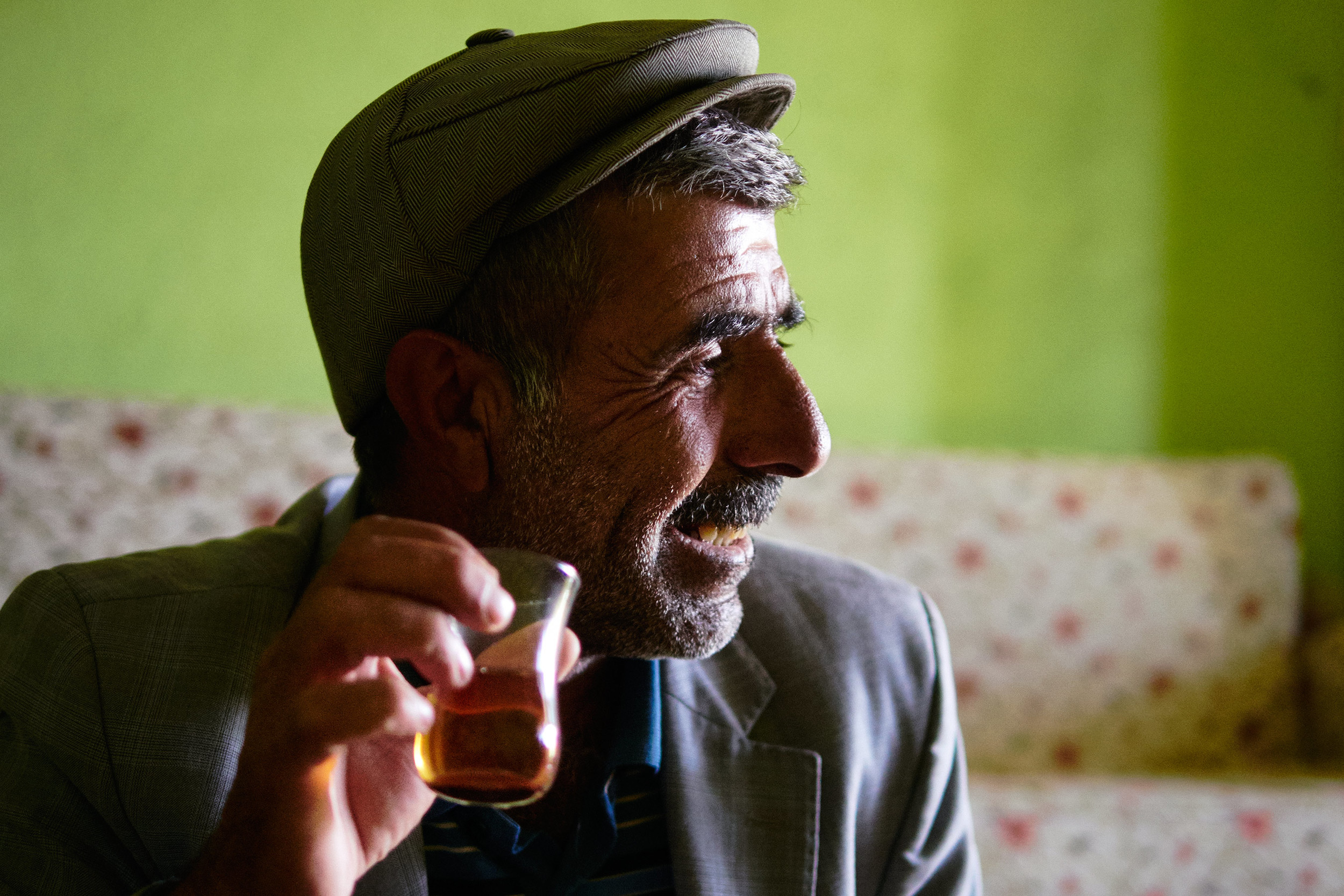 Mustafa having tea and smiling