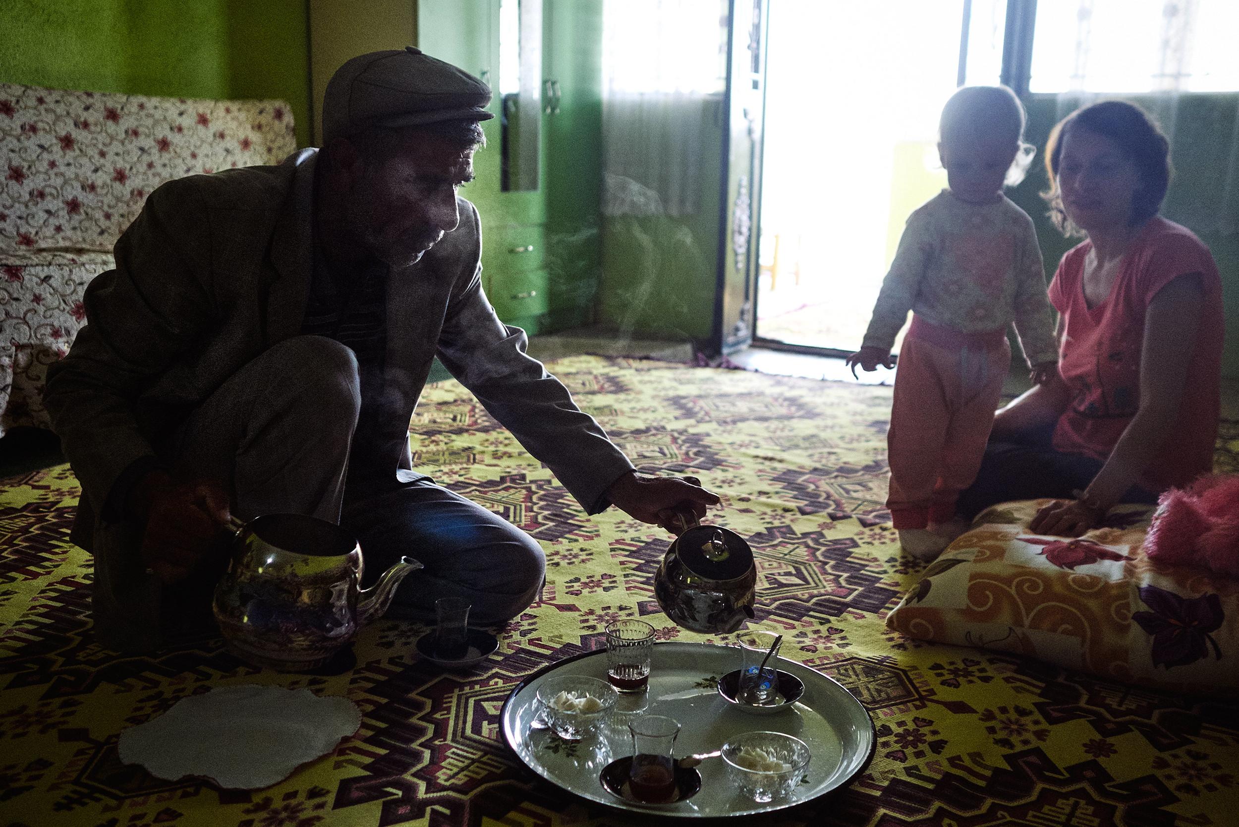 Mustafa pouring tea while Mia watches