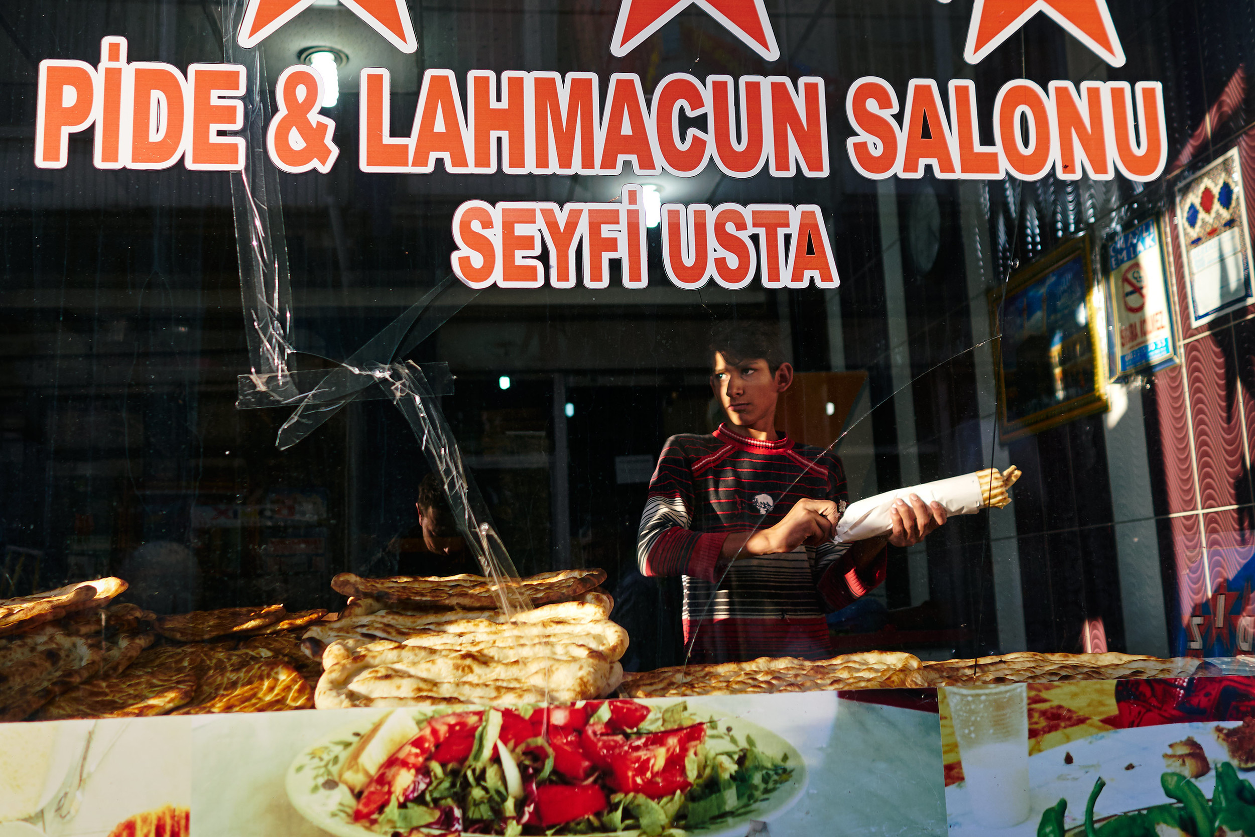 "A boy packing pide for a customer in a ""Pide and Lahmazun Saloon"" as they call them here."
