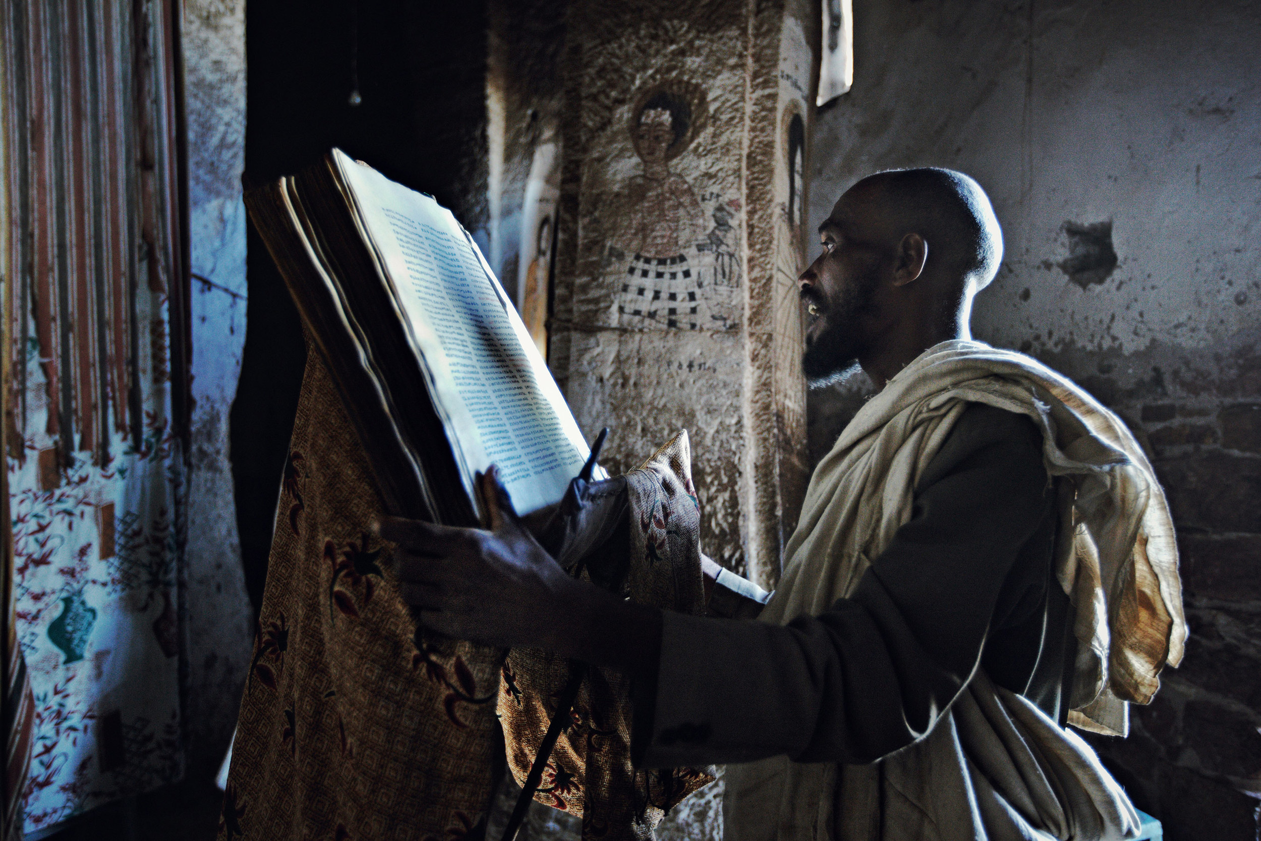 Ethiopian Orthodox Christian man reading from a prayer book