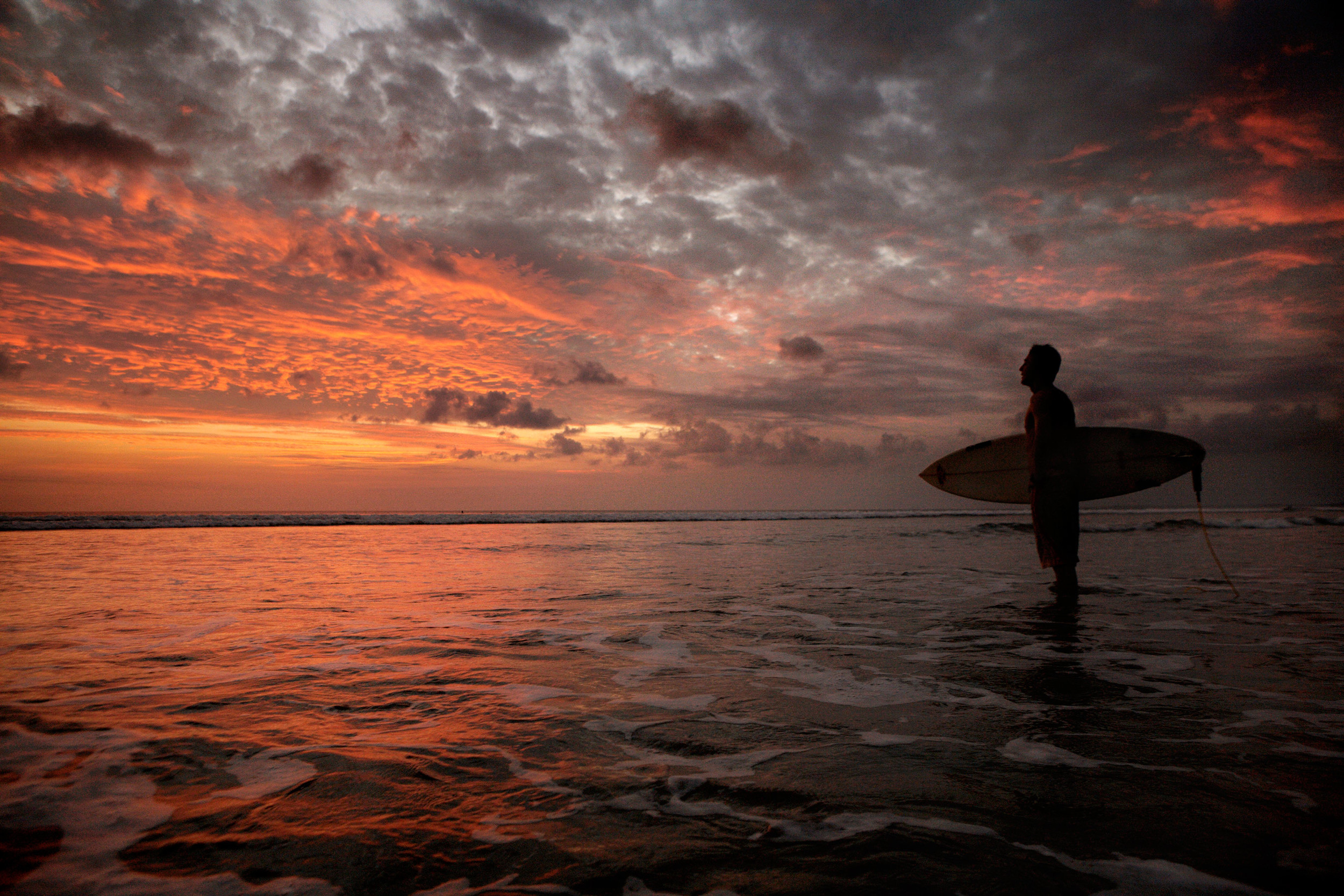 Surfer looks at the twilight sky in Bali
