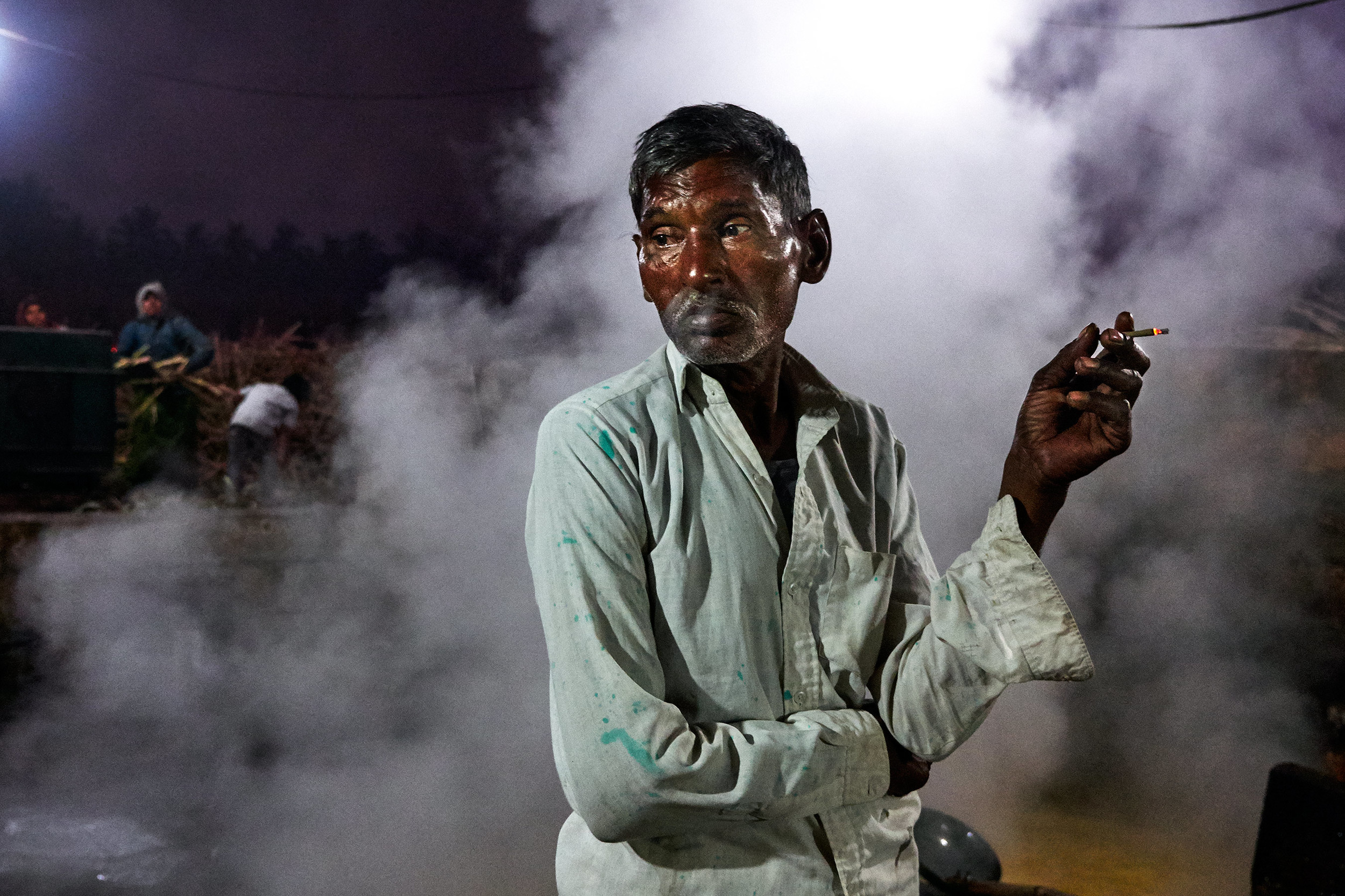 Sugarcane worker by the vat and smoke