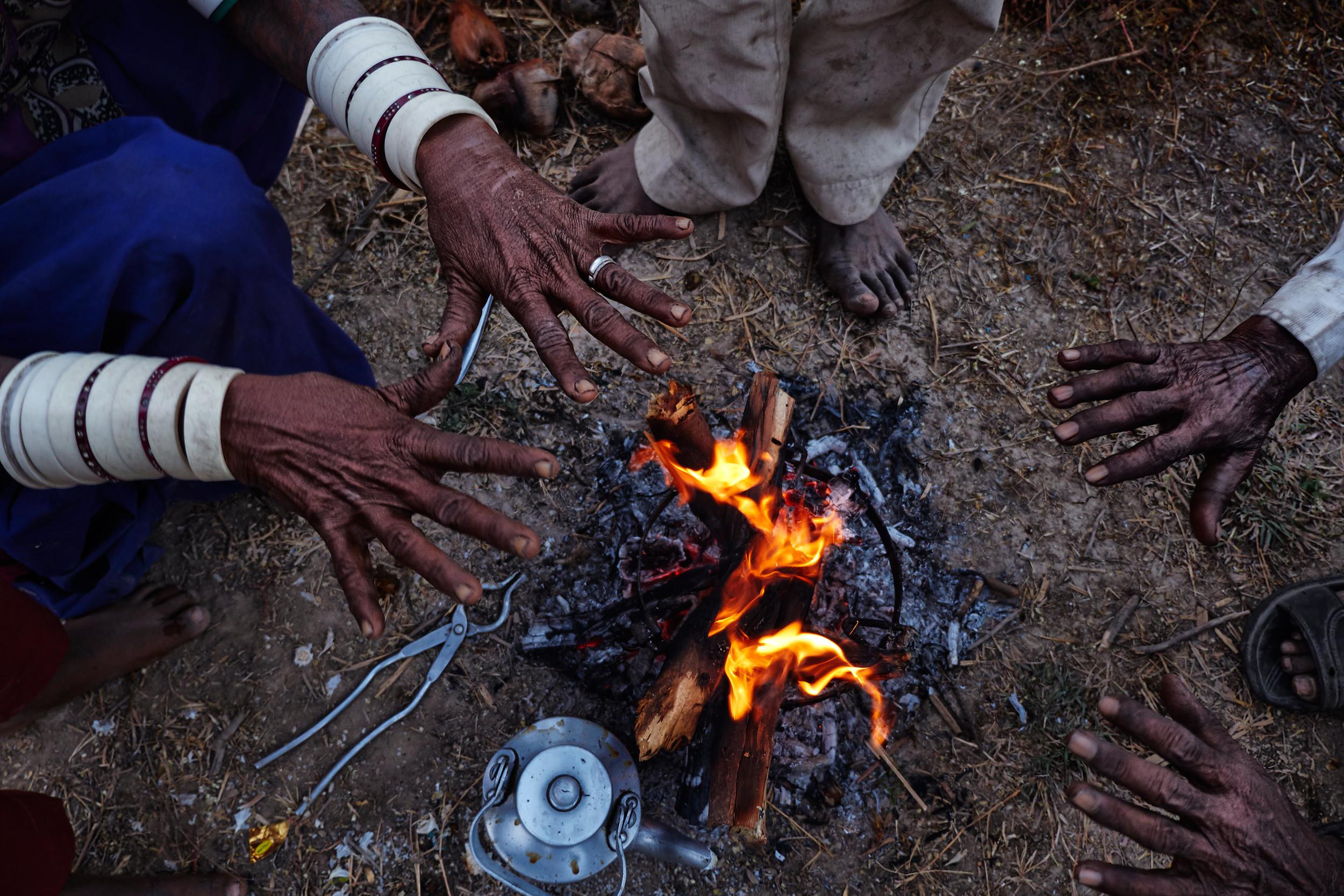 Nomads' hands around a fire