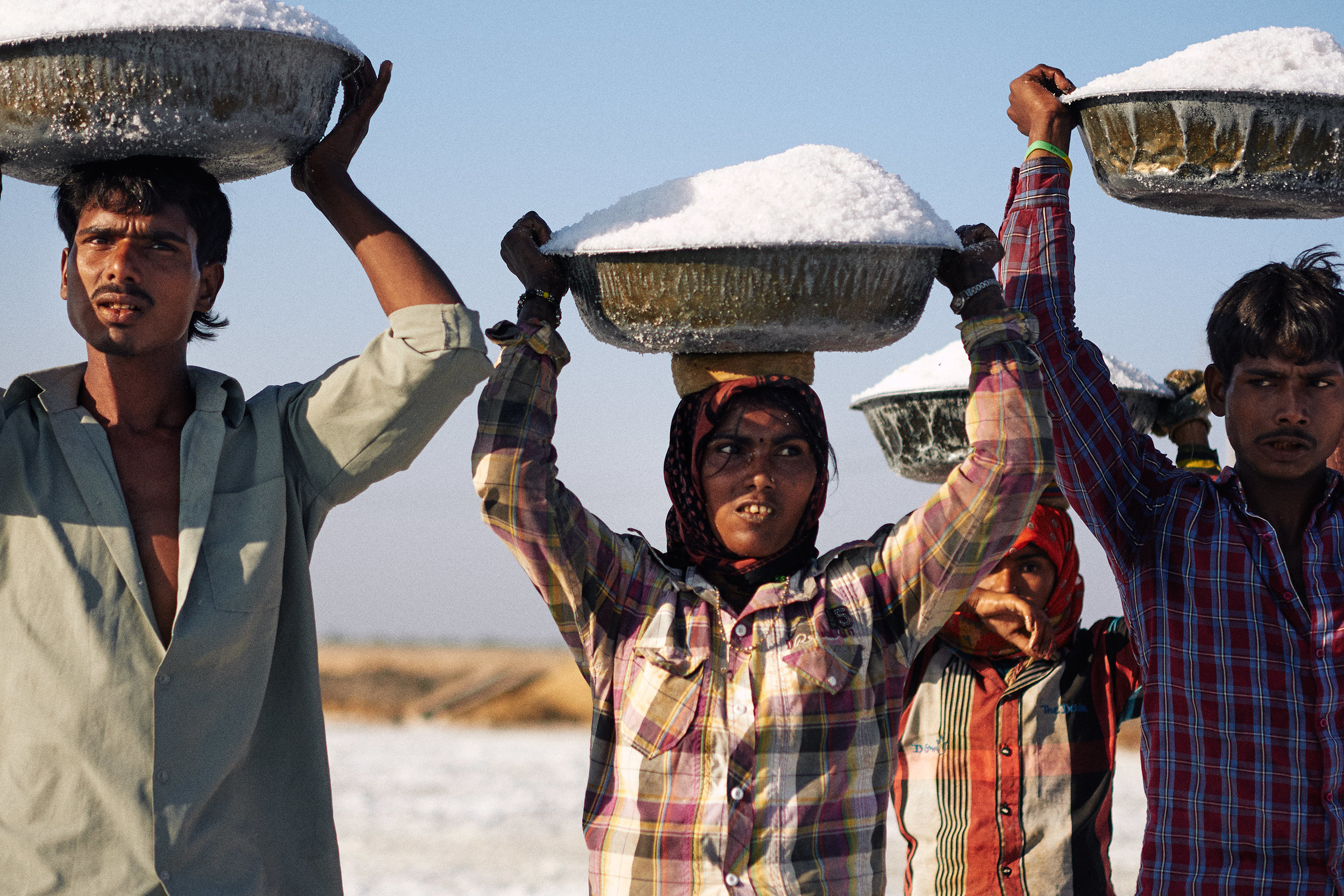 Salt workers with tubs of salt on their heads