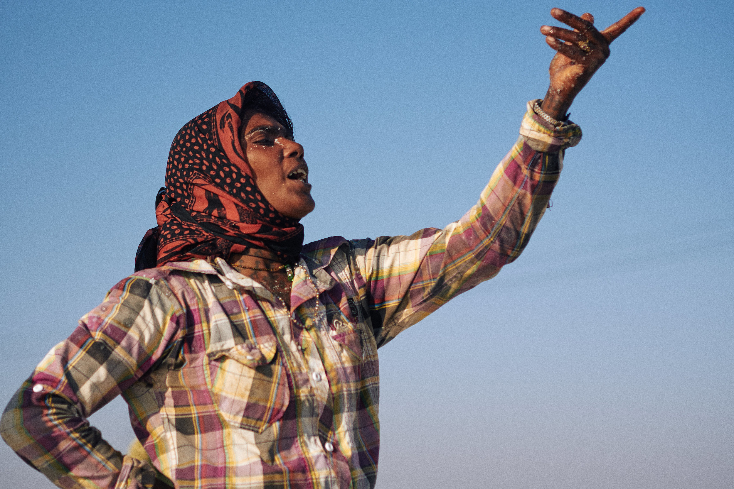 Woman salt worker communicates with her team