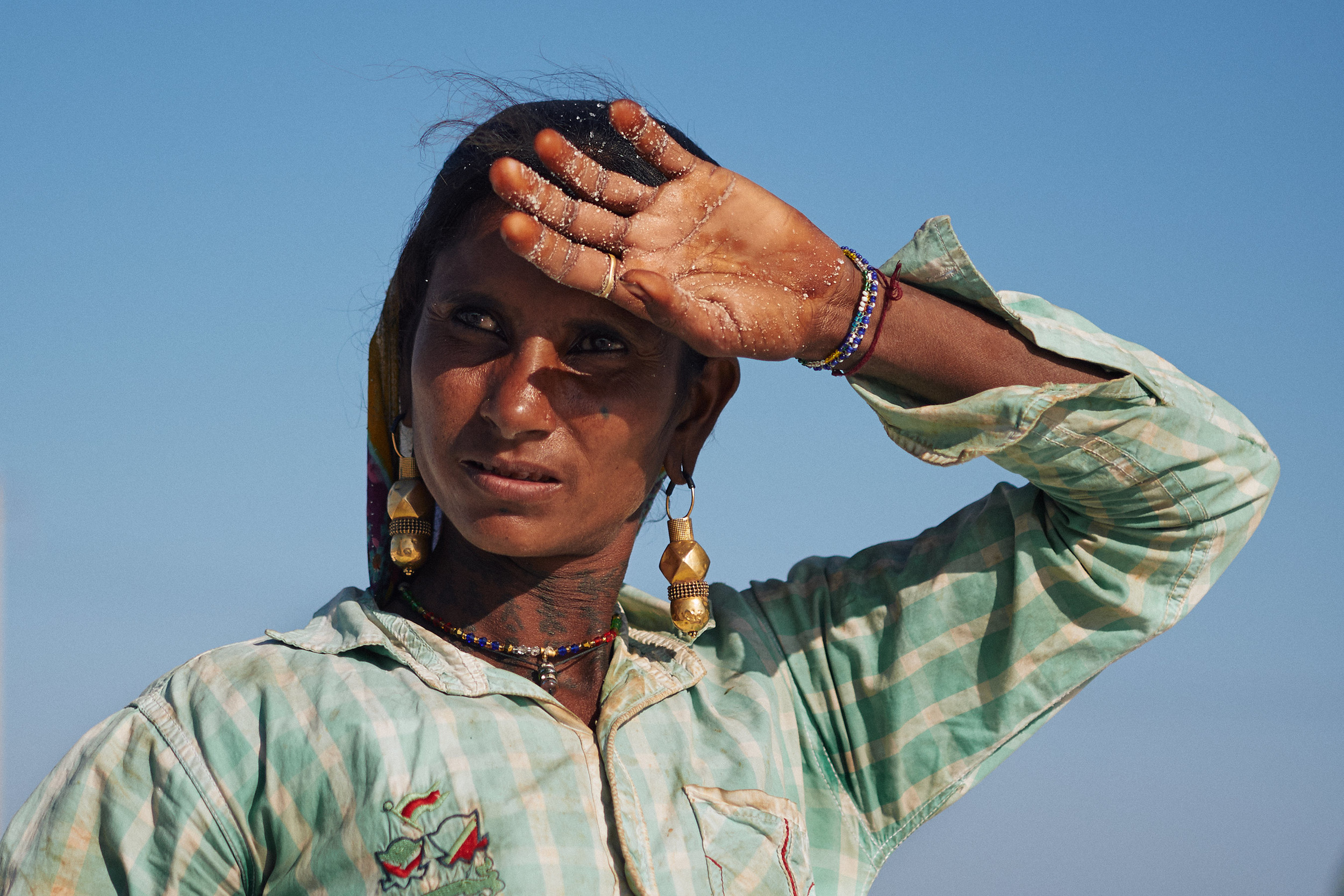 Woman salt worker wiping sweat off her forehead
