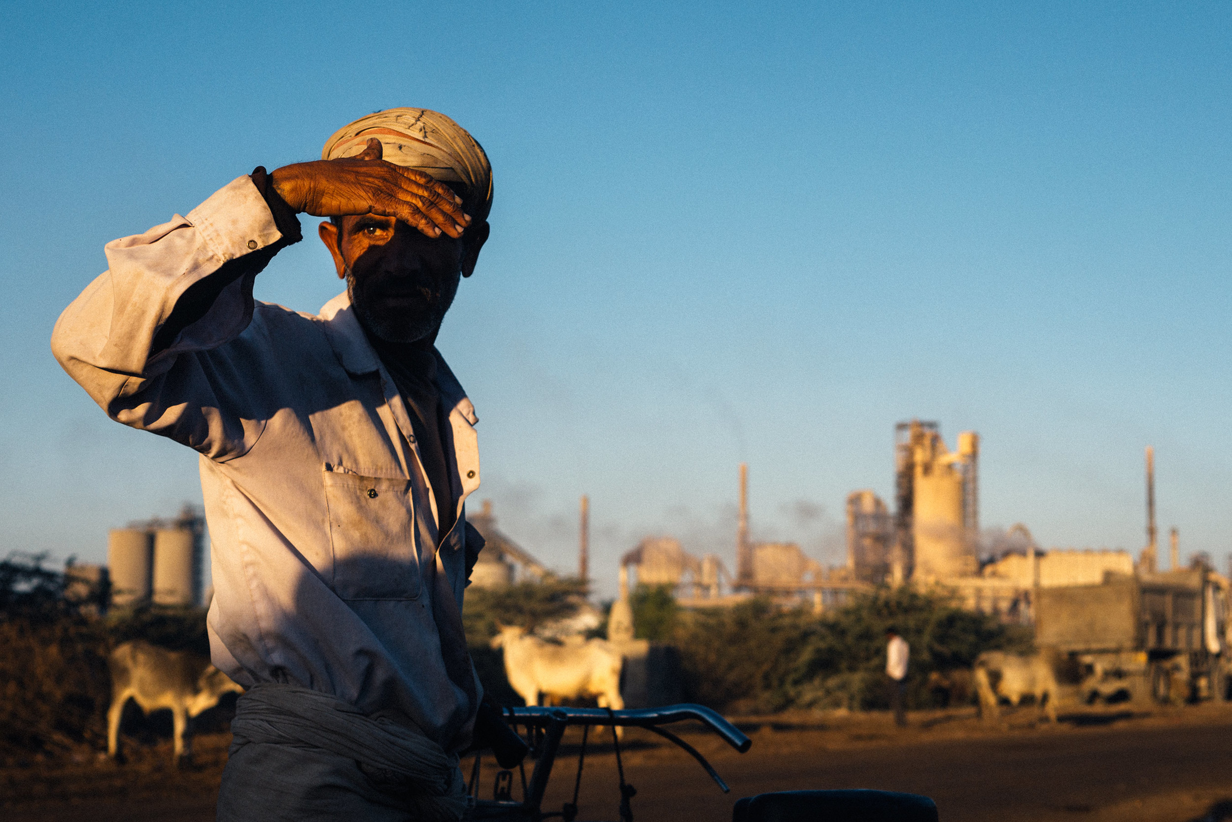 Man with bicycle in front of chemical plant
