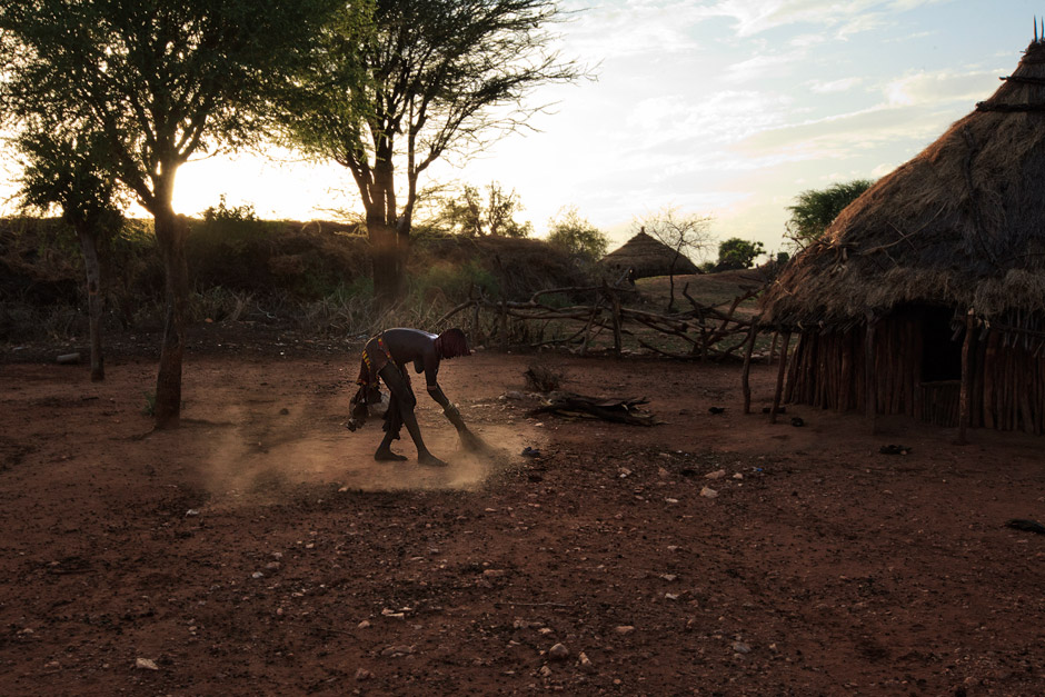 Hamer woman sweeping the grounds of her family compound