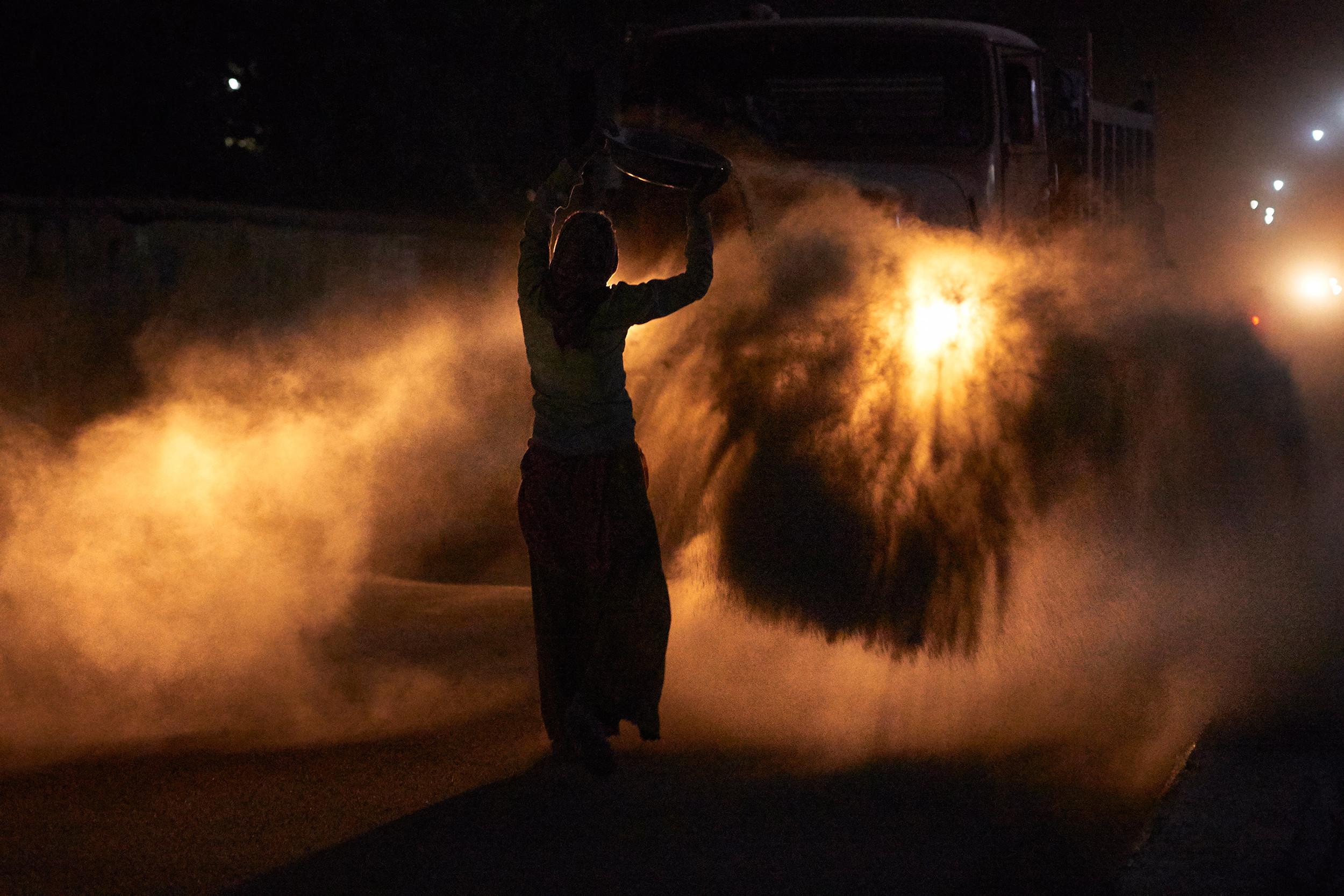 Woman road worker spraying sand over asphalt