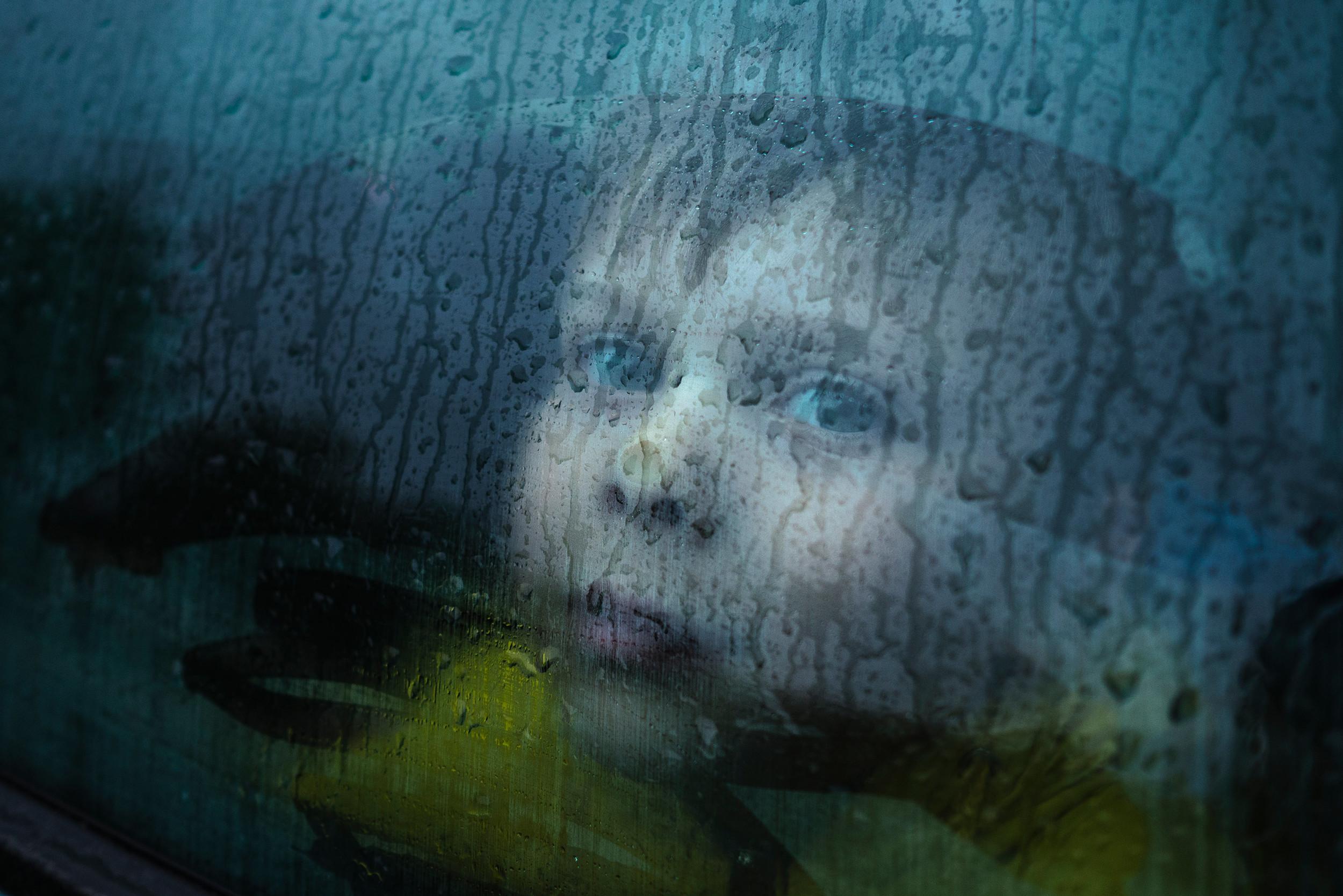 Belarusian boy pressing his head against a car window