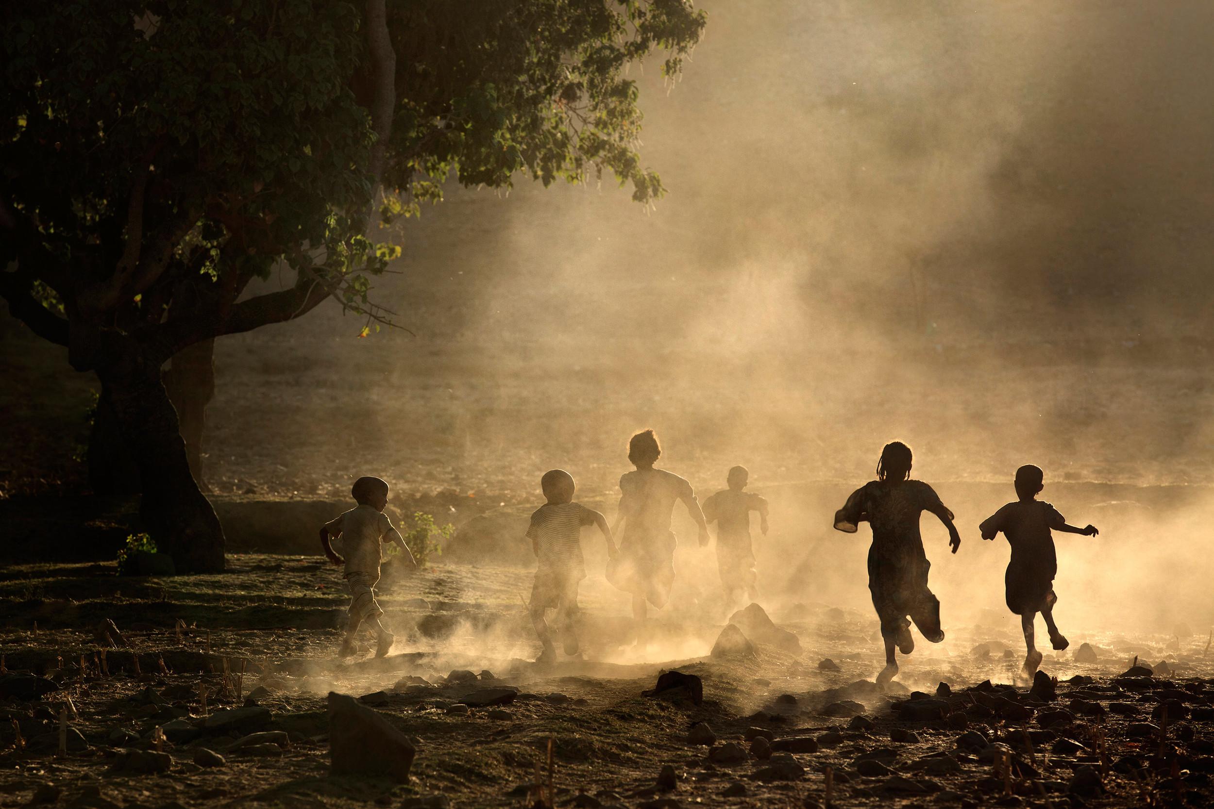 Tigrayan children kicking up dust at sunset