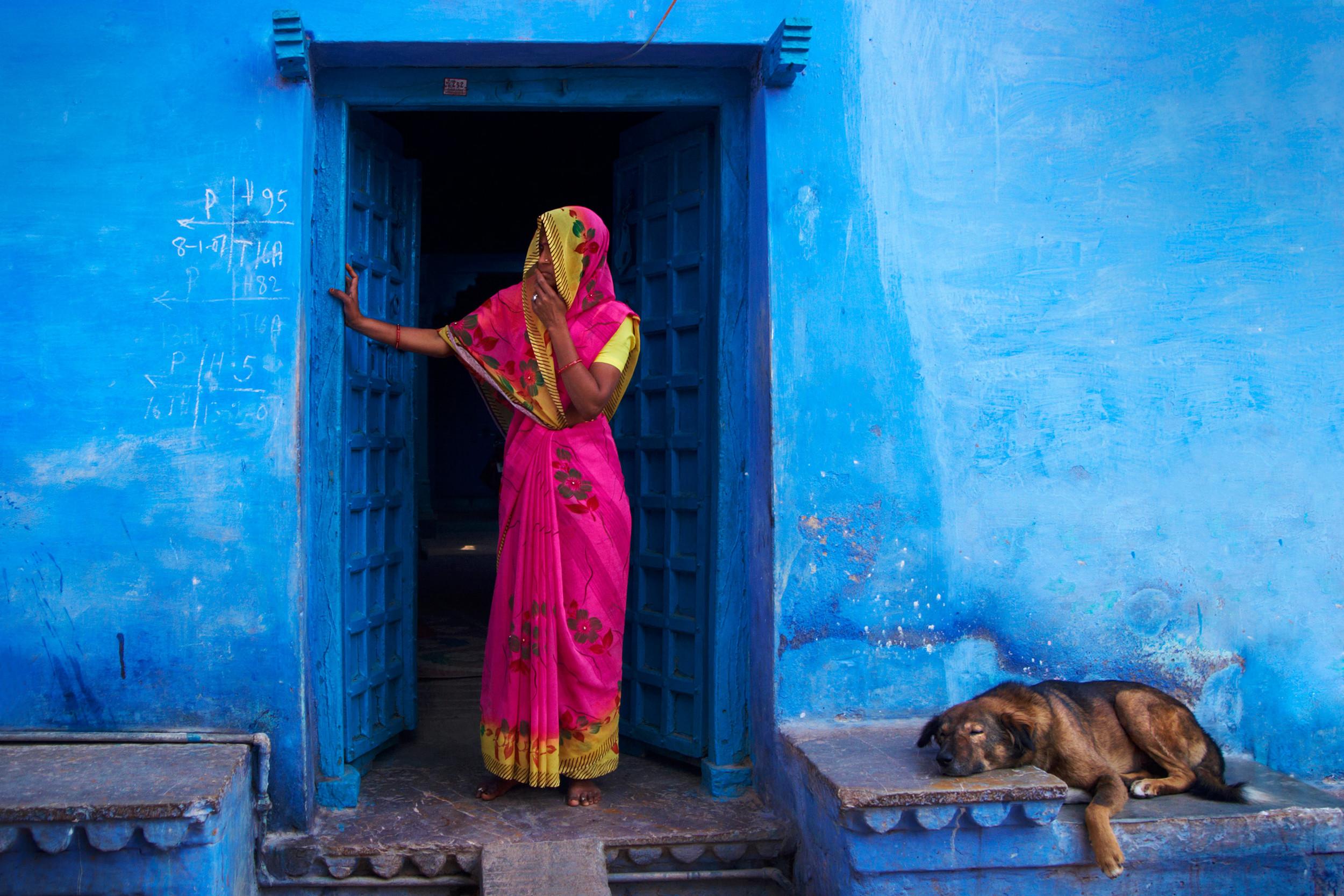 Rajasthani woman against a blue house