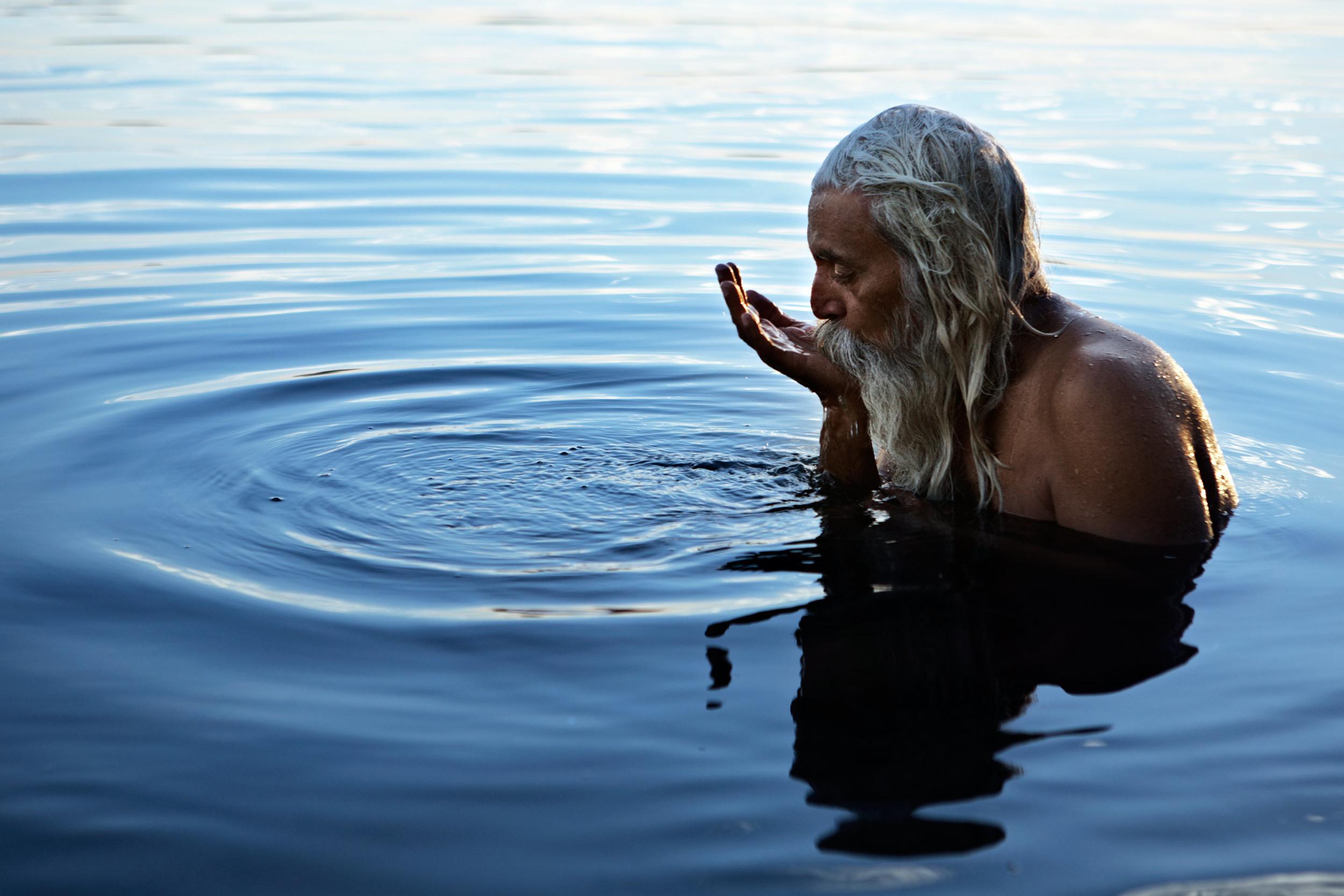 Hindu holyman bathing and drinking from the Narmada