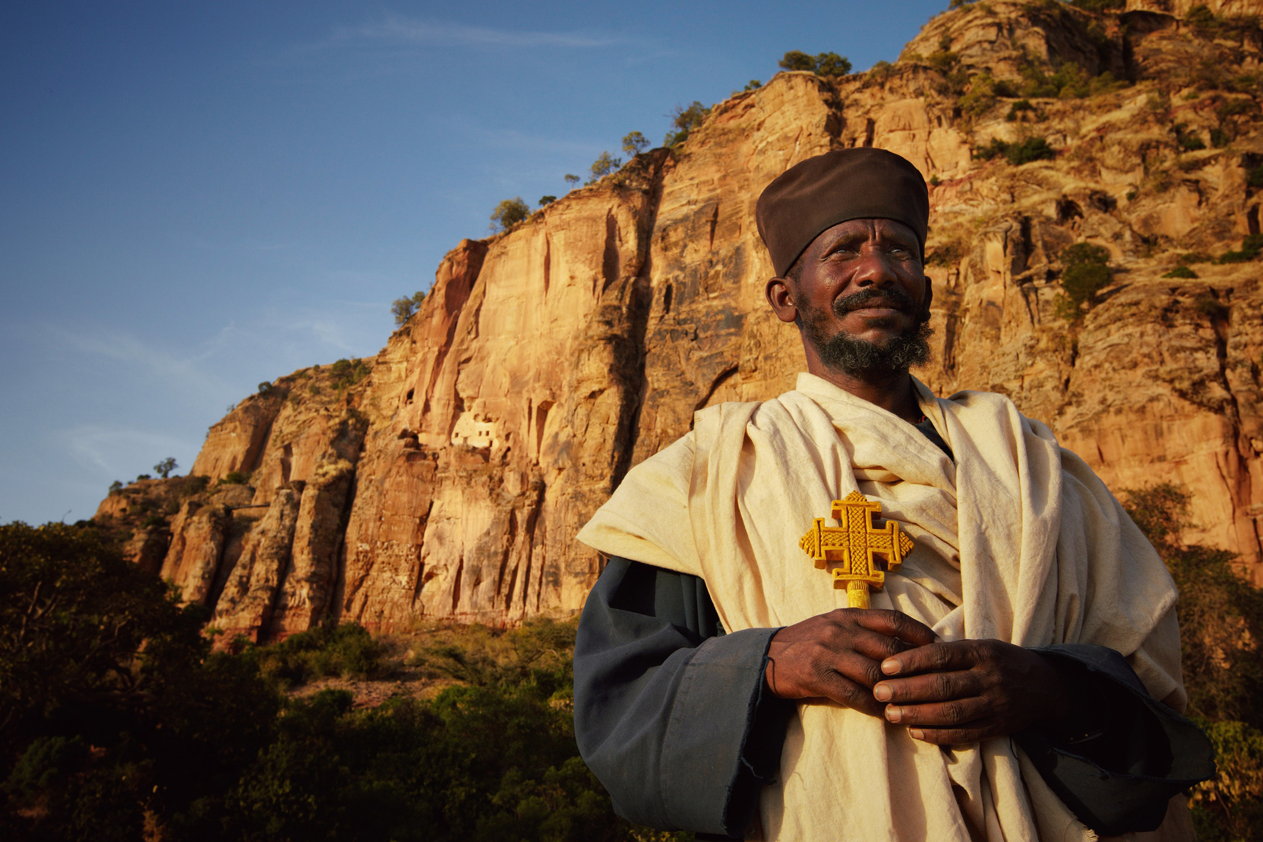 Ethiopian priest in front of a cliff with a rock church carved in it