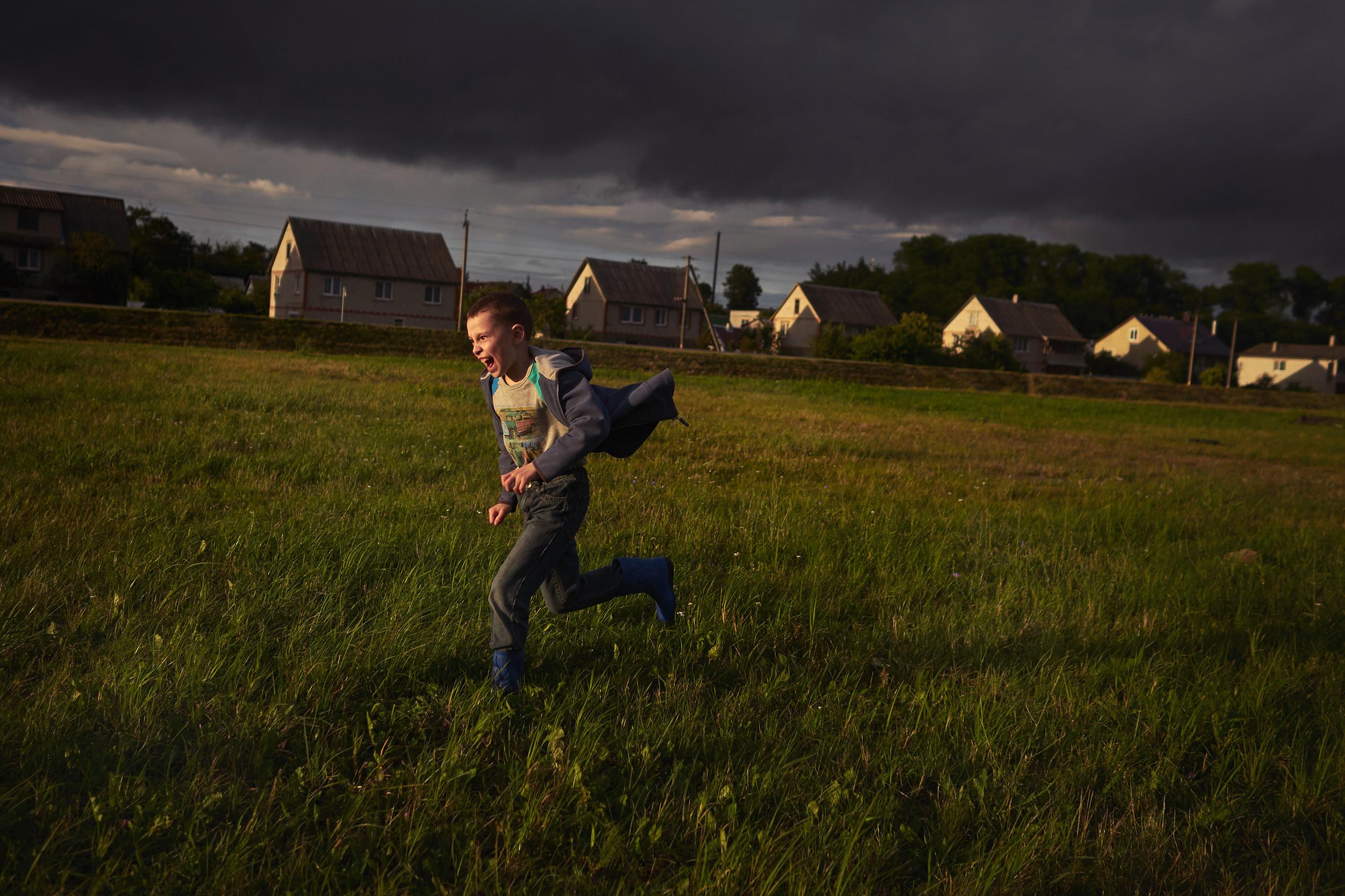 Boy running across a field in Belarus