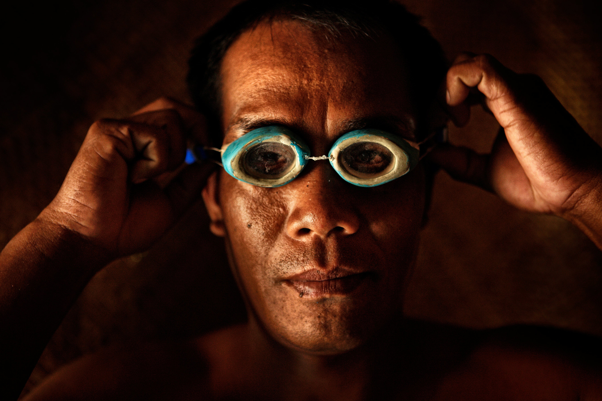 Filippino fisherman putting on traditional goggles
