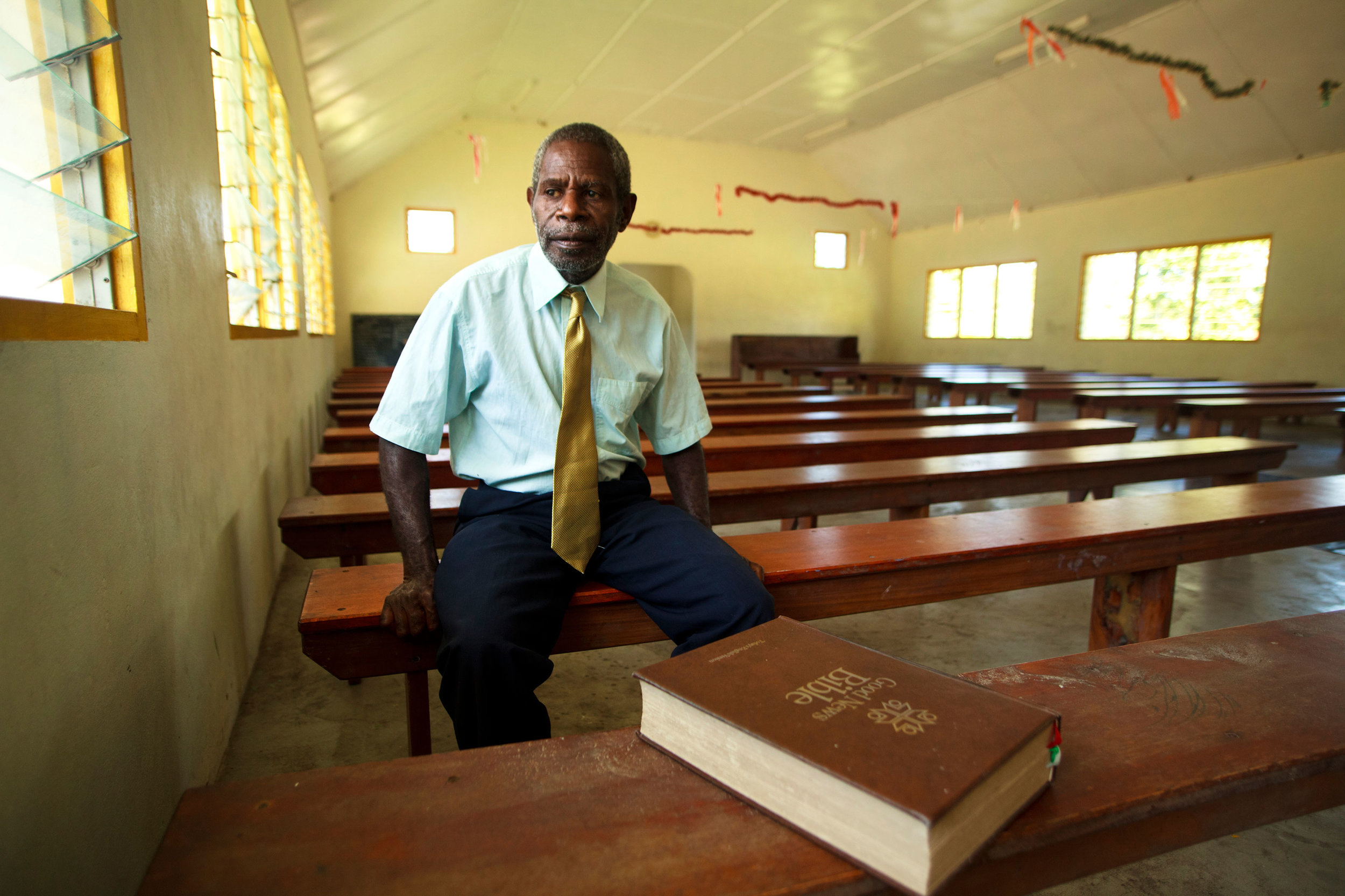 Ayar in his role as the village elder sitting in a church after Sunday Mass.