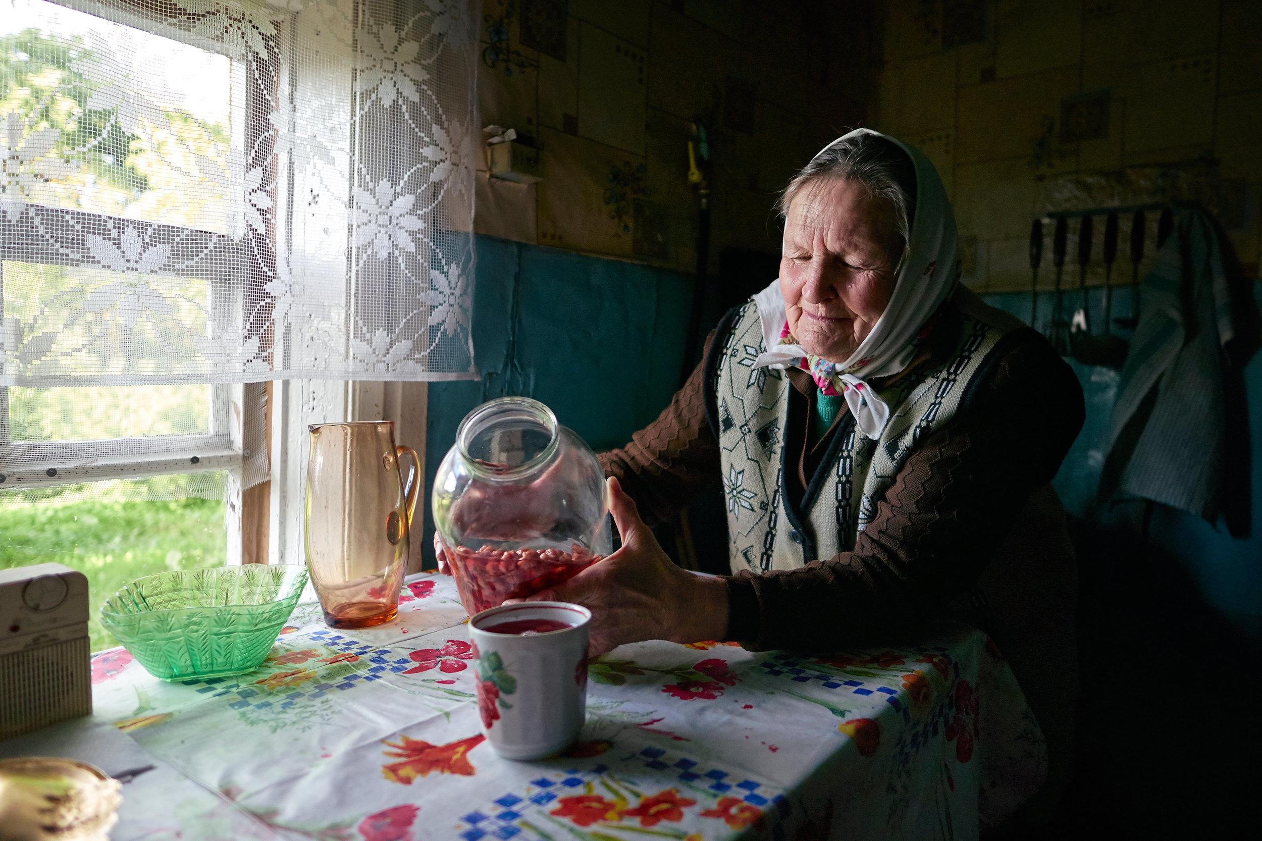 Braslav-Belarus-elderly-woman-pours-rasberry-juice