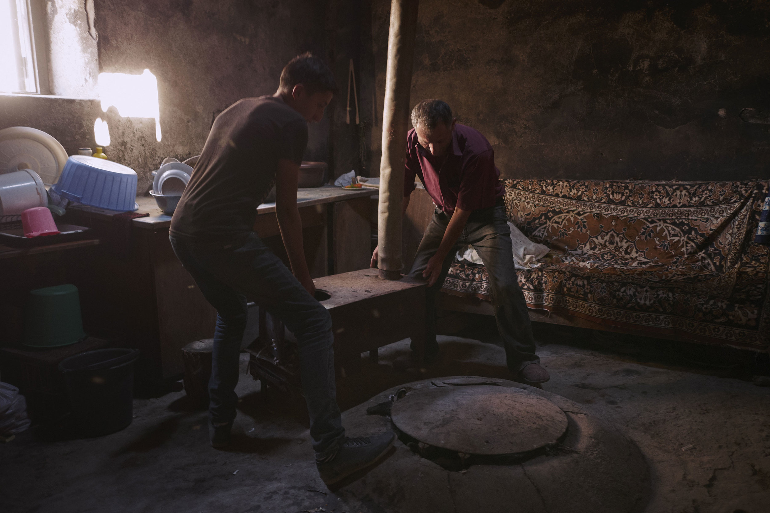 Armenia-father-and-son-lifting-up-an-oven
