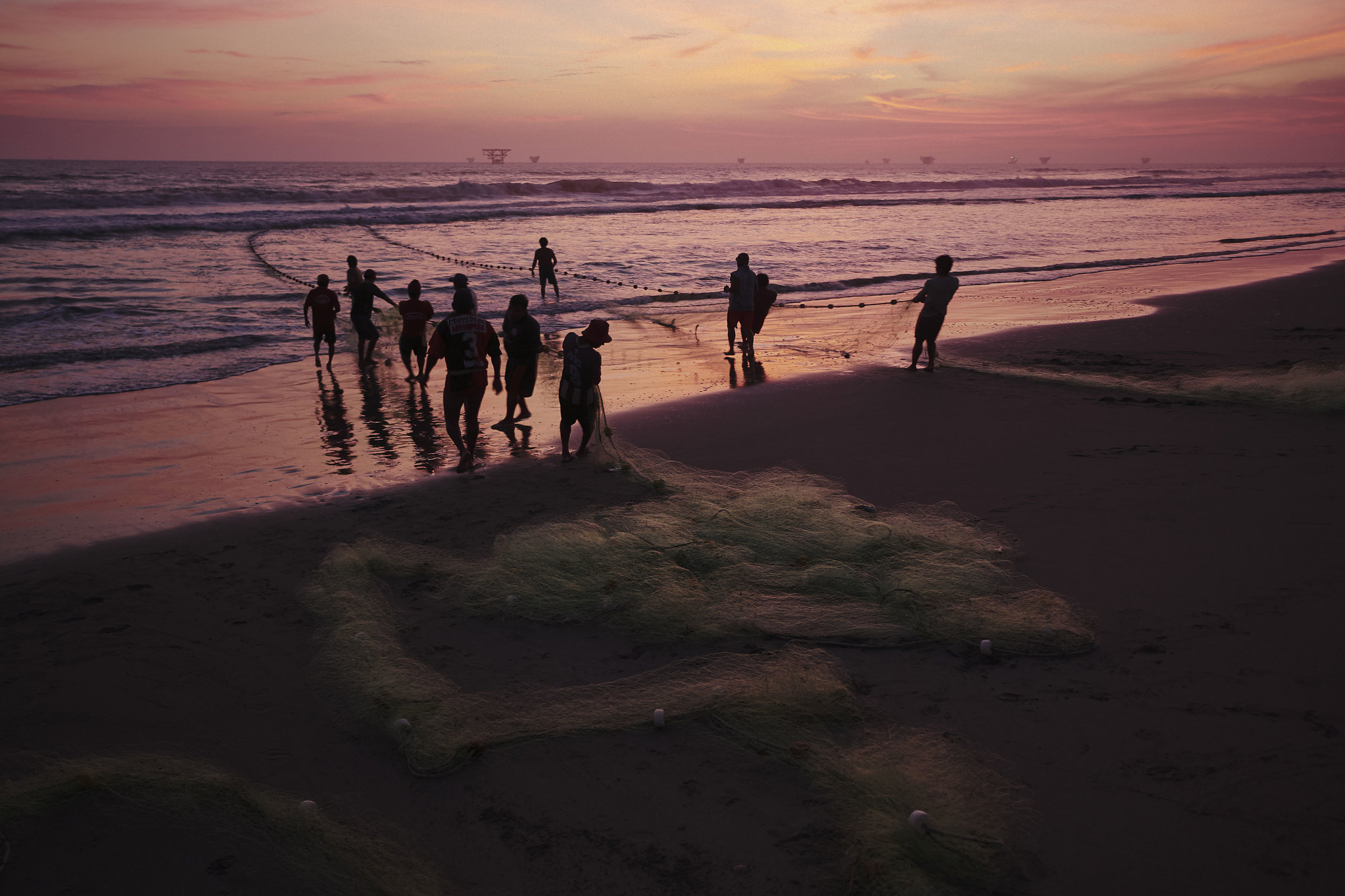 Fishermen pulling out the net from the ocean Peru