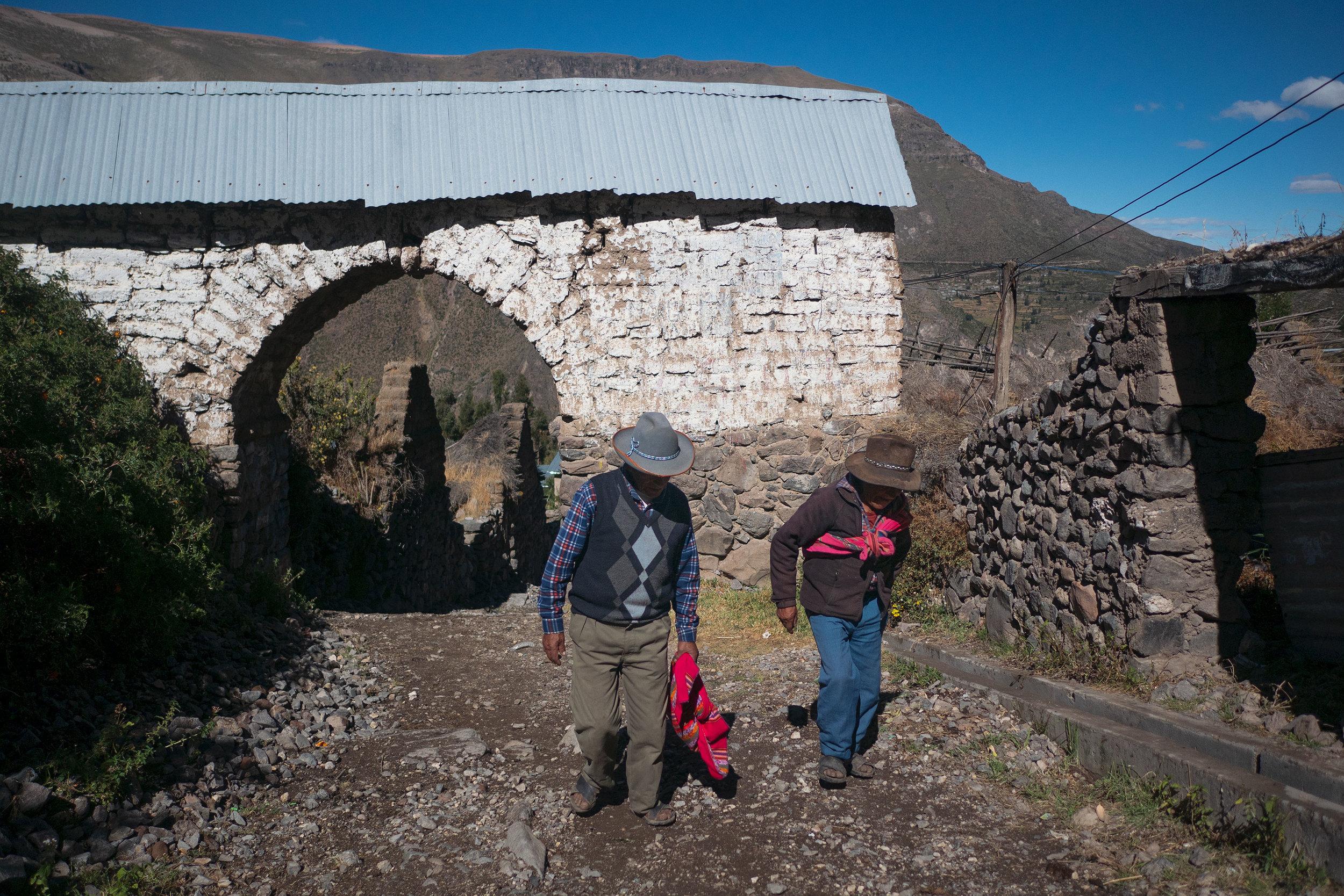 Men against an ancient arch in Puica, Peru