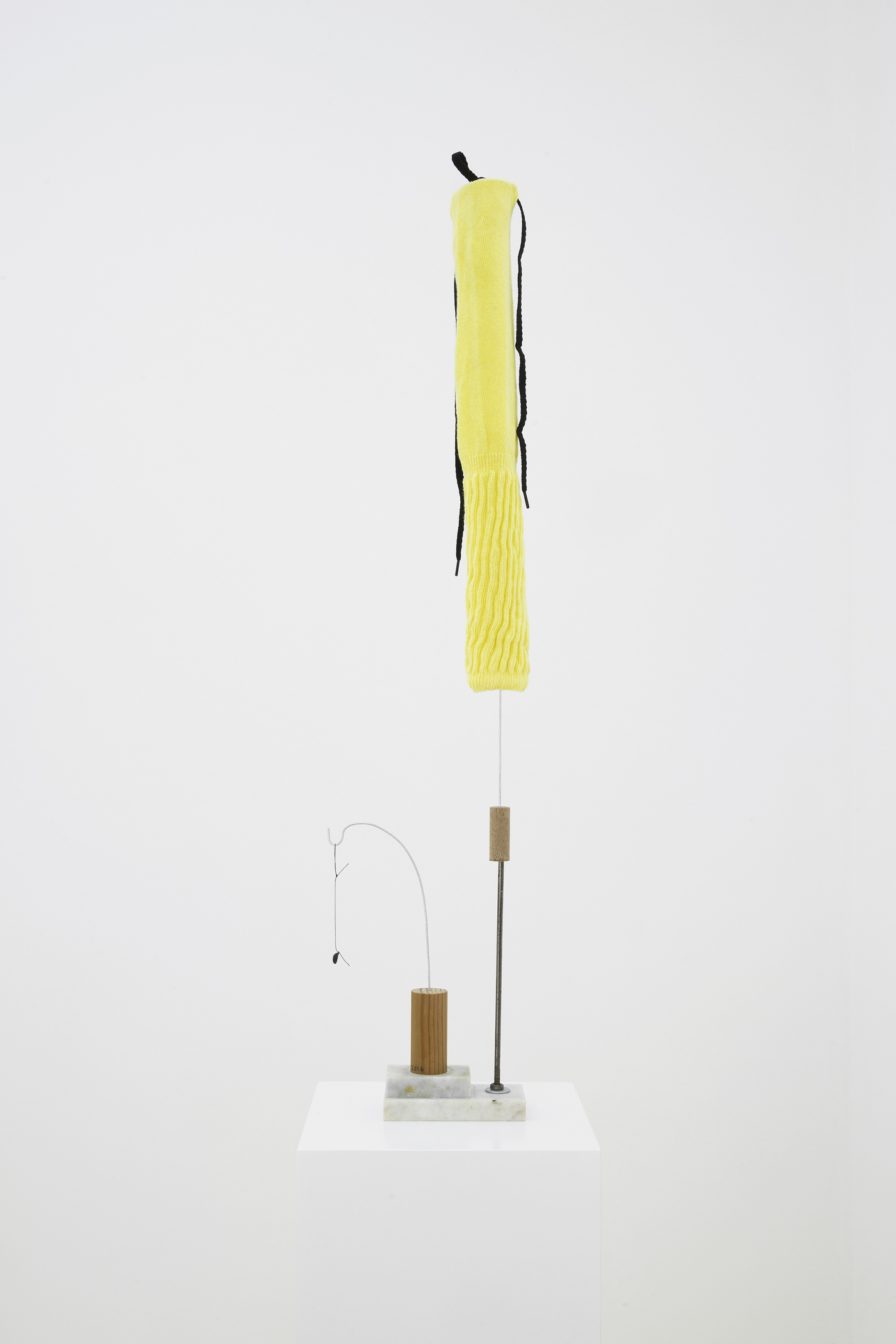 Untitled (Yellow sock), 2016, Cotton sock, shoelace, shoe button, marble, wire, metal, wood, and thread, 85.5 x 19 x 6.5 cm (34 x 7.5 x 2.5 in)