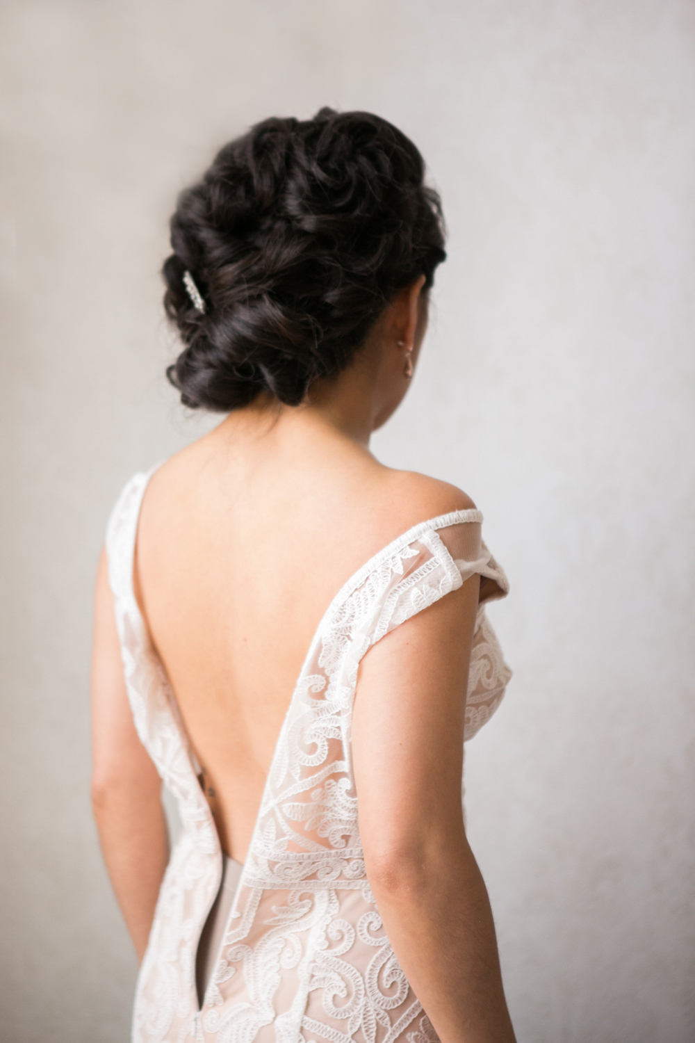 Lesbian Black tie wedding in New York City; here Kat puts on her BHLDN gown.