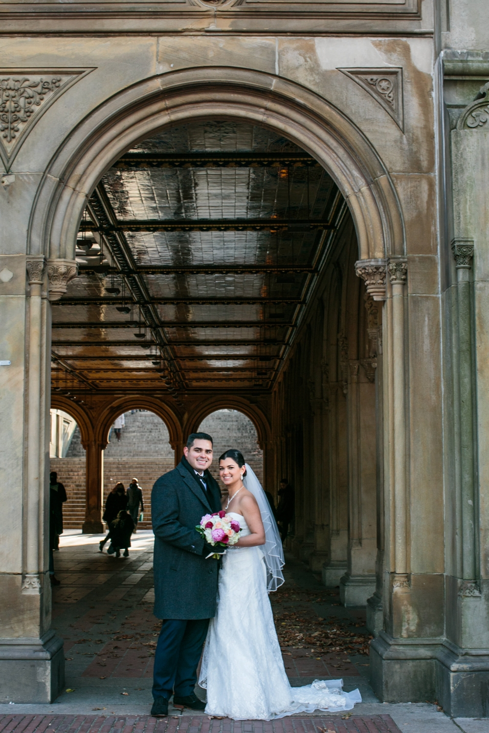 Bride and groom smiling under beautiful arch