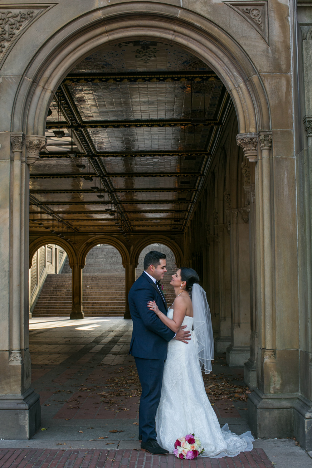 Bride and groom together under arch