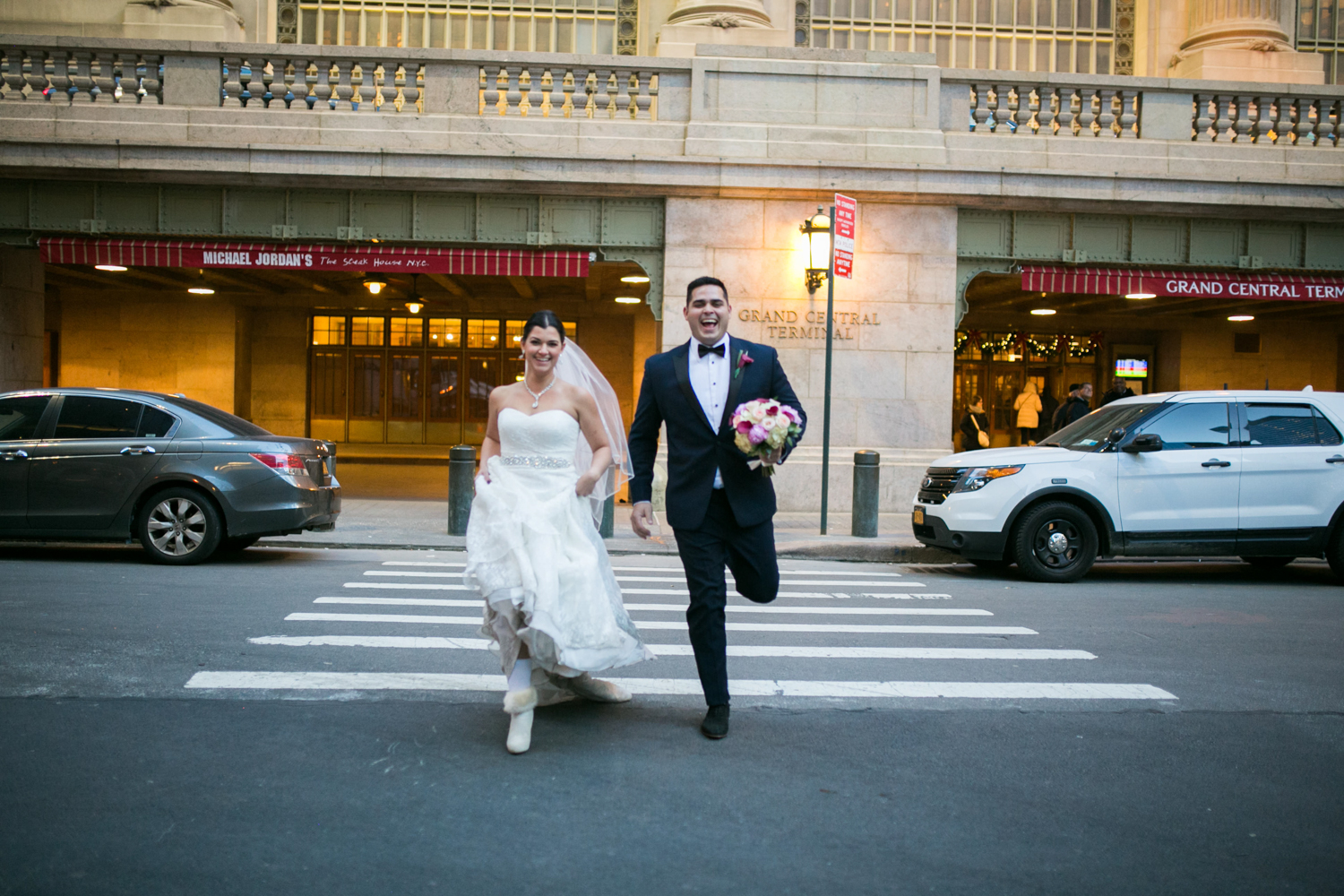 Bride and groom running in front of grand central terminal