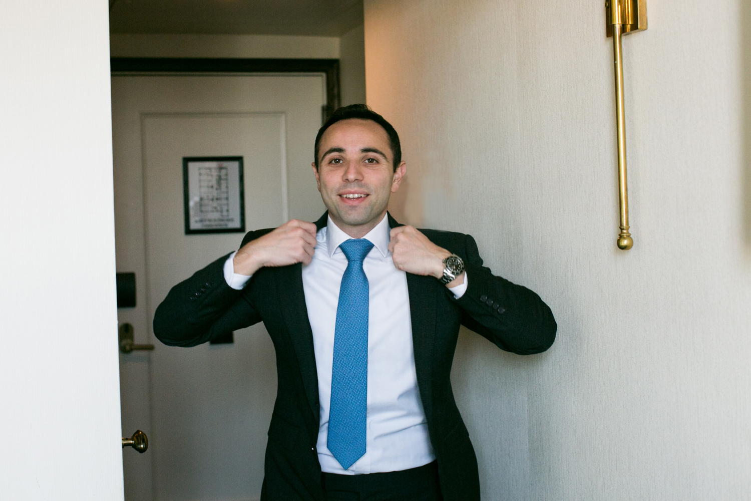 Photo of groom putting on his Ralph Lauren Suit