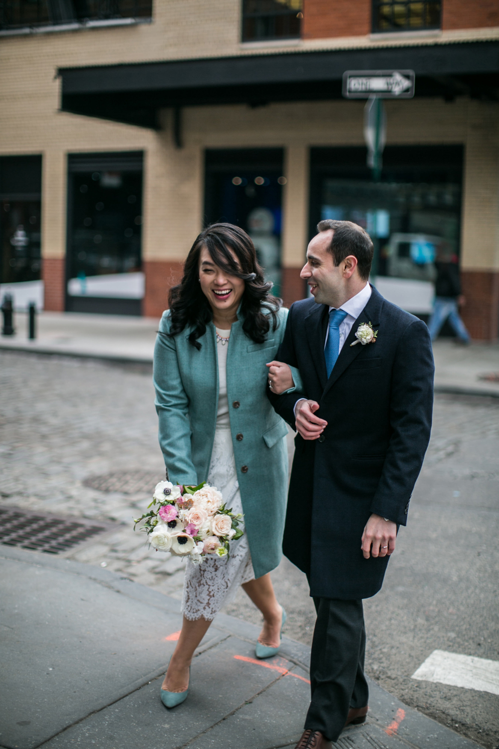 Bride laughing as she walks through NYC with groom