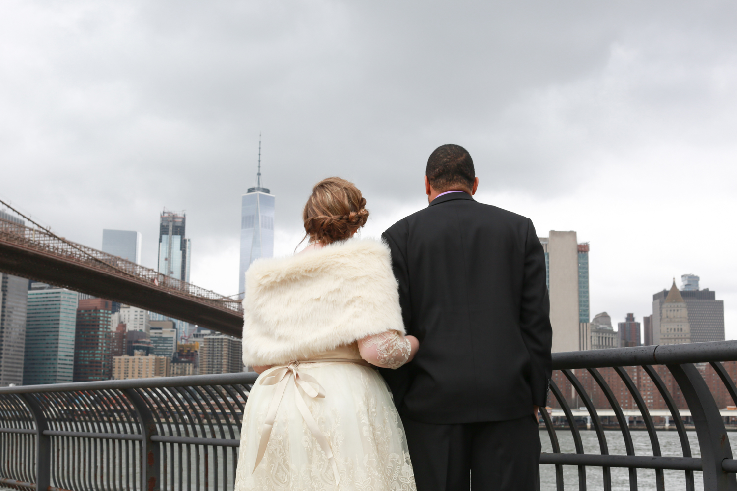 Bride and groom look over the water in NYC