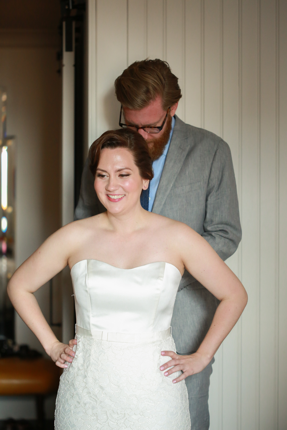 Groom helping his bride get ready for NYC elopement