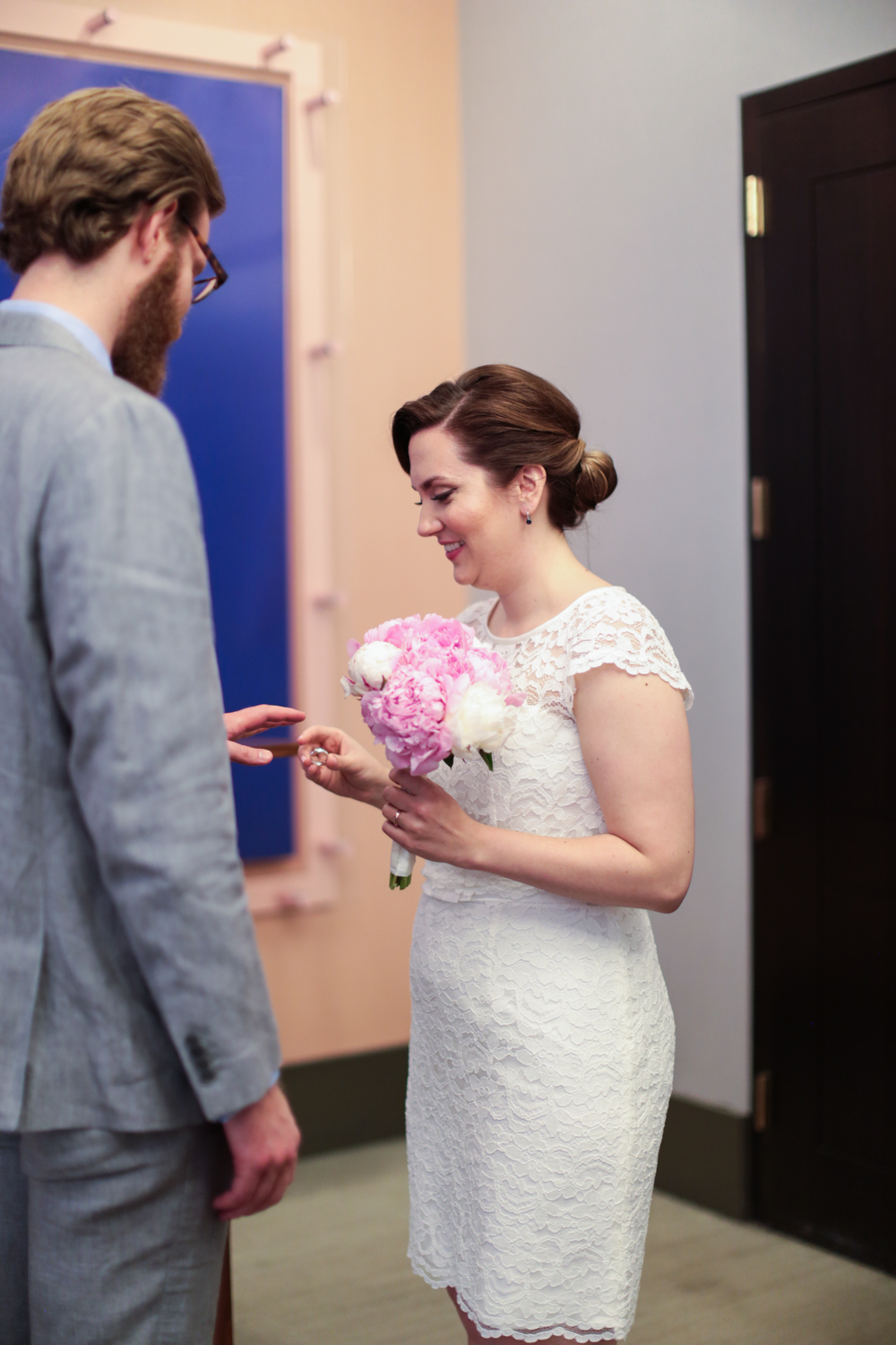 Bride places ring on grooms finger during elopement