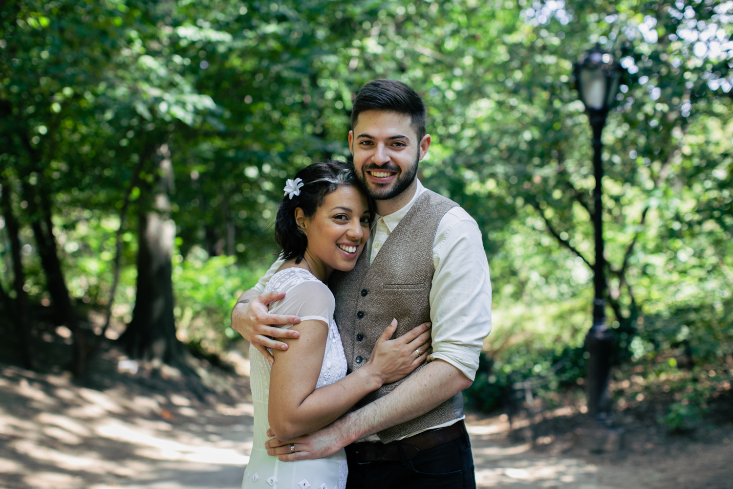 New York City newlyweds embrace in the park.