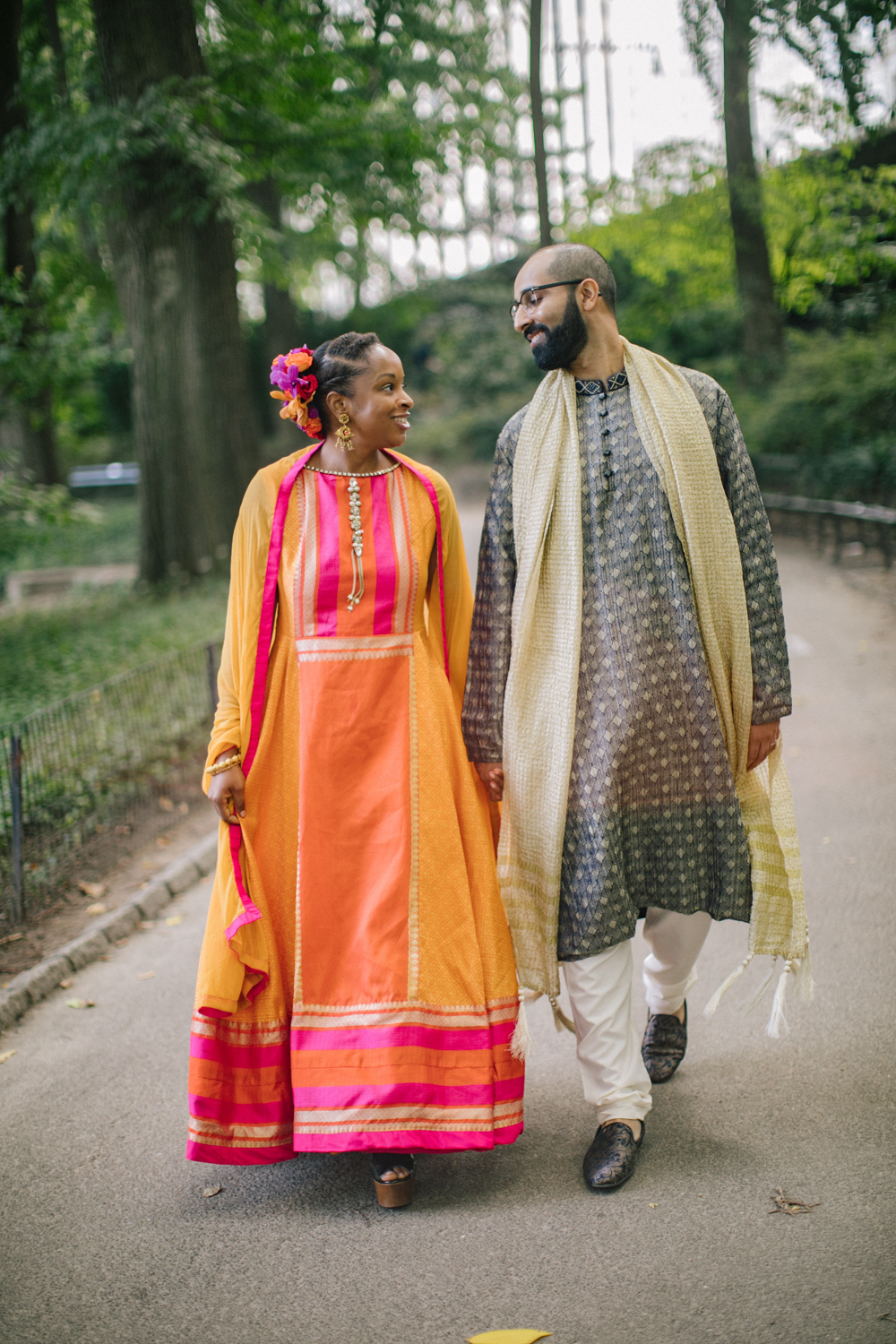 Bride and groom hold hands while walking together through Central Park.