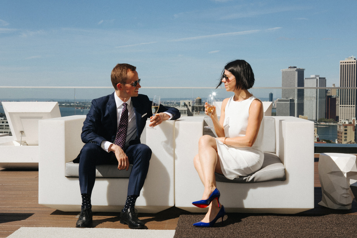 Chic bride and groom sip champagne while overlooking Manhattan.