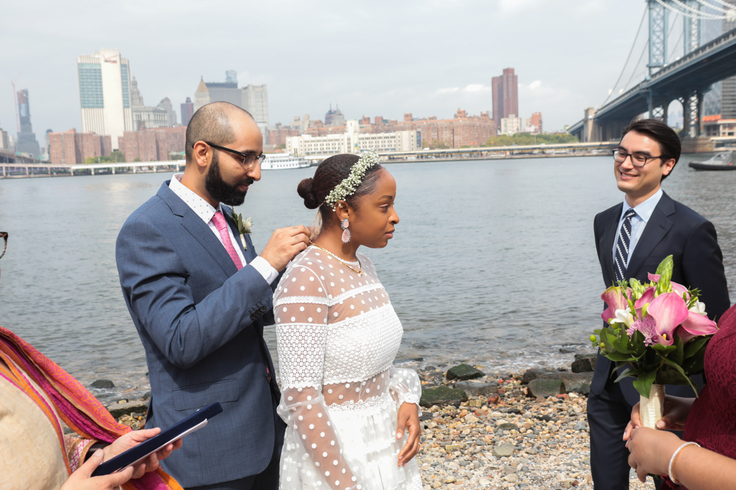 The groom places a necklace on the bride in a Brooklyn Bridge Park Wedding Ceremony