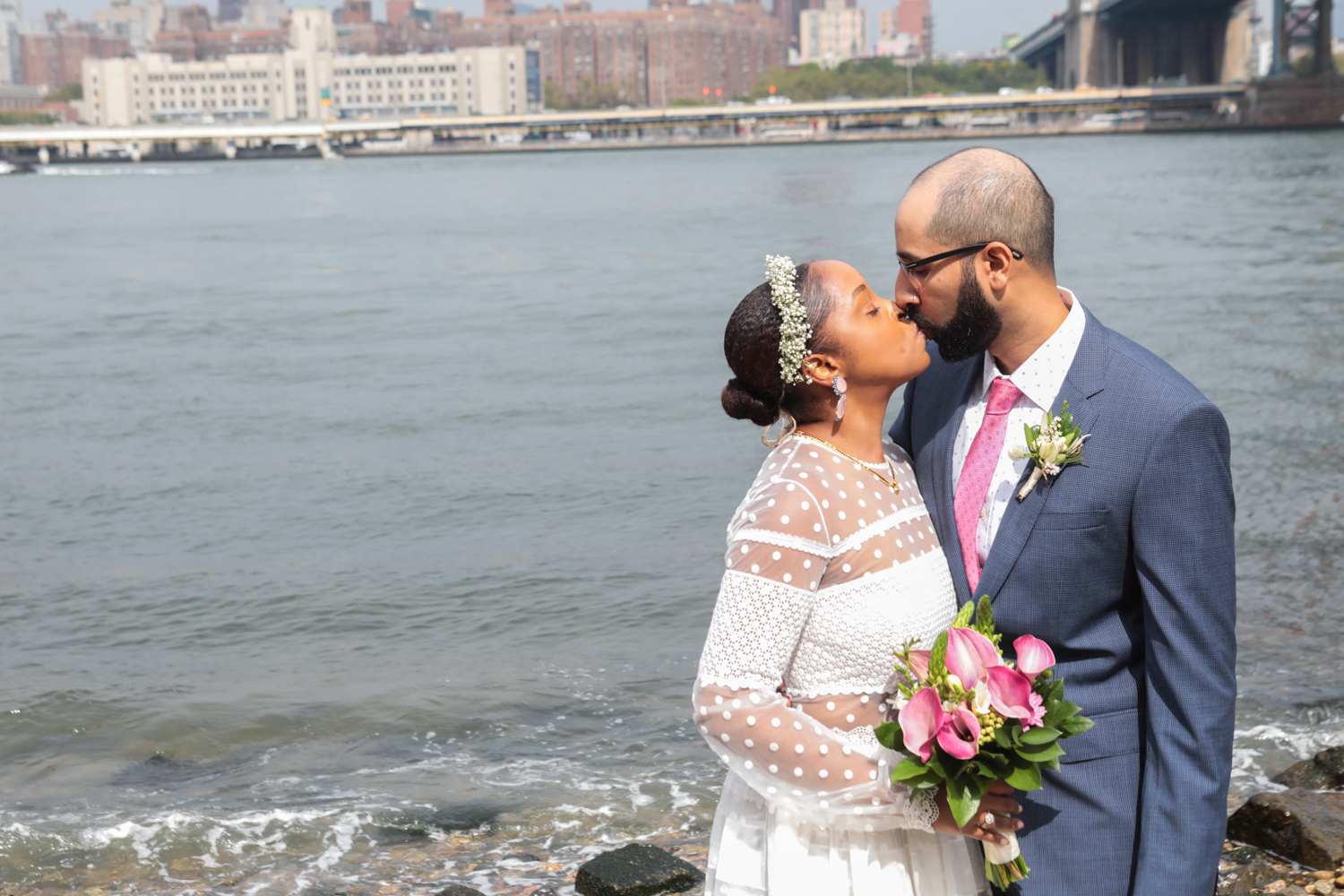 The bride and groom kiss in Brooklyn Bridge Park after their wedding ceremony.