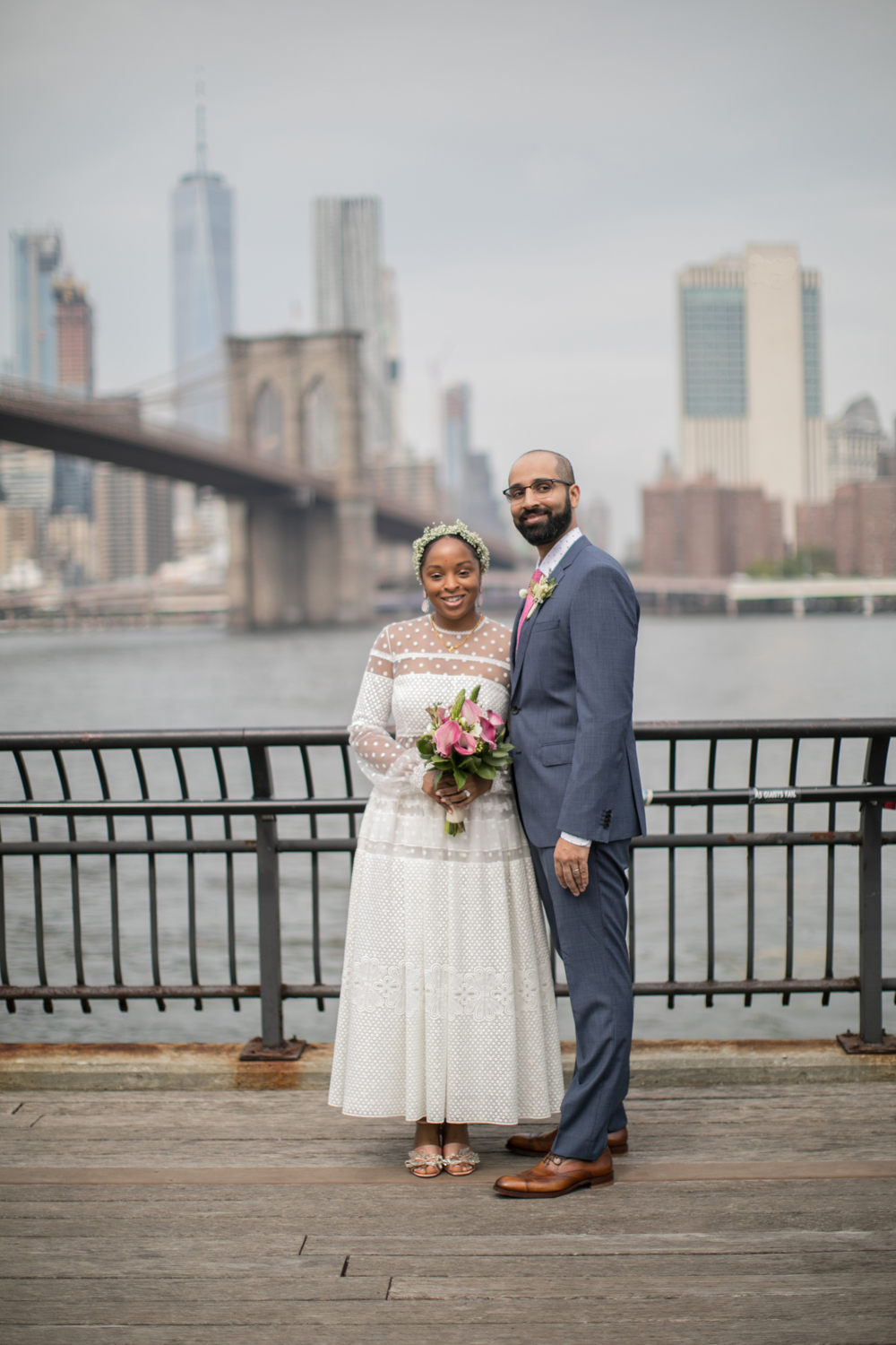 Bride and groom pose together in Brooklyn Bridge Park